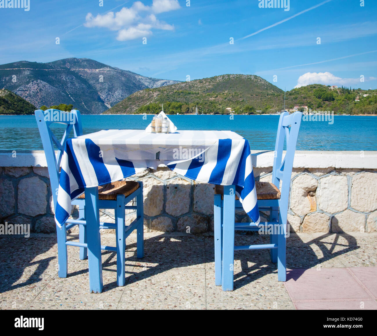 Blue table with two chairs plus Greek flag tablecloth in a restaurant by the sea in Vathy the capital of Ithaca - Stock Image