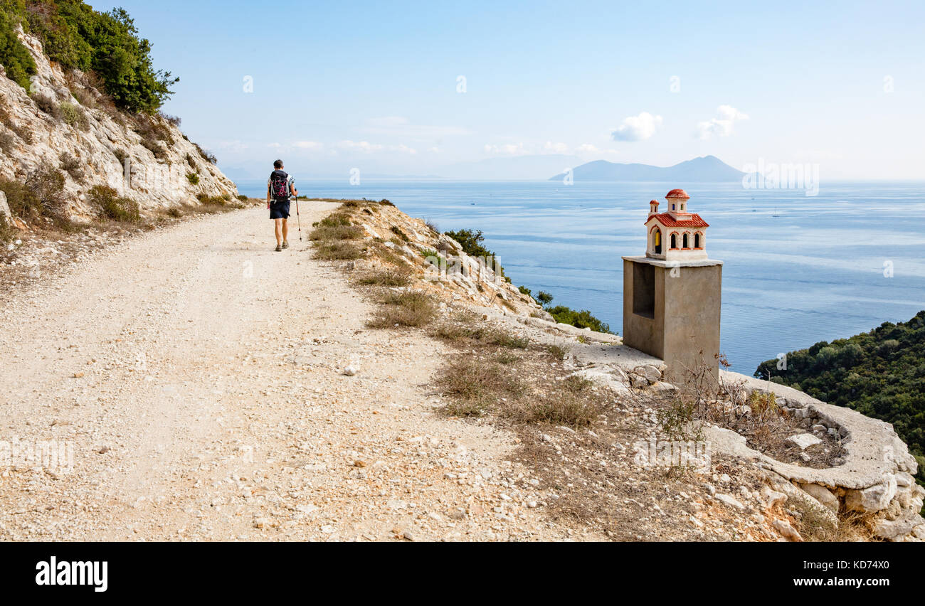 A female walker passing a roadside shrine in the form of a church on the island of Ithaka in the Ionian Islands Stock Photo