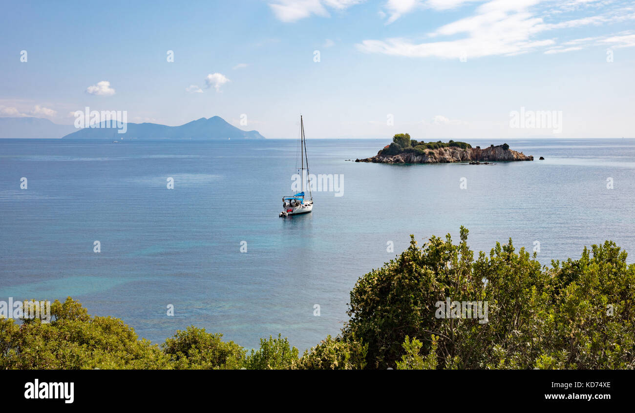 Peaceful scene on the Ionian island of Ithaka in Greece with yacht and the little island of Agios Nikolaos at Marmaka - Stock Image