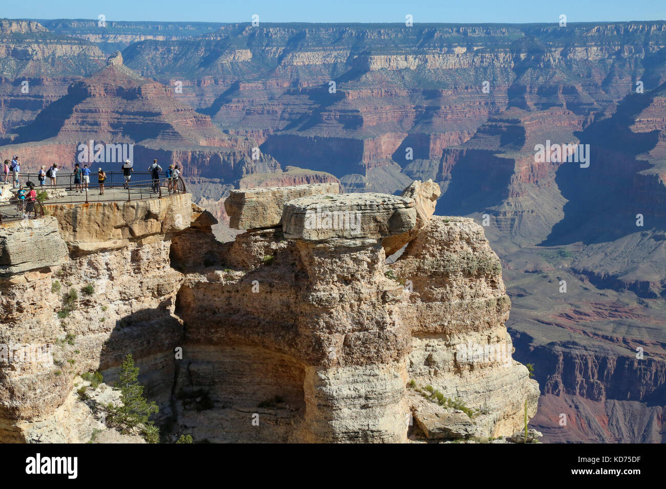Tourists atop observation area on south rim of Grand Canyon - Stock Image