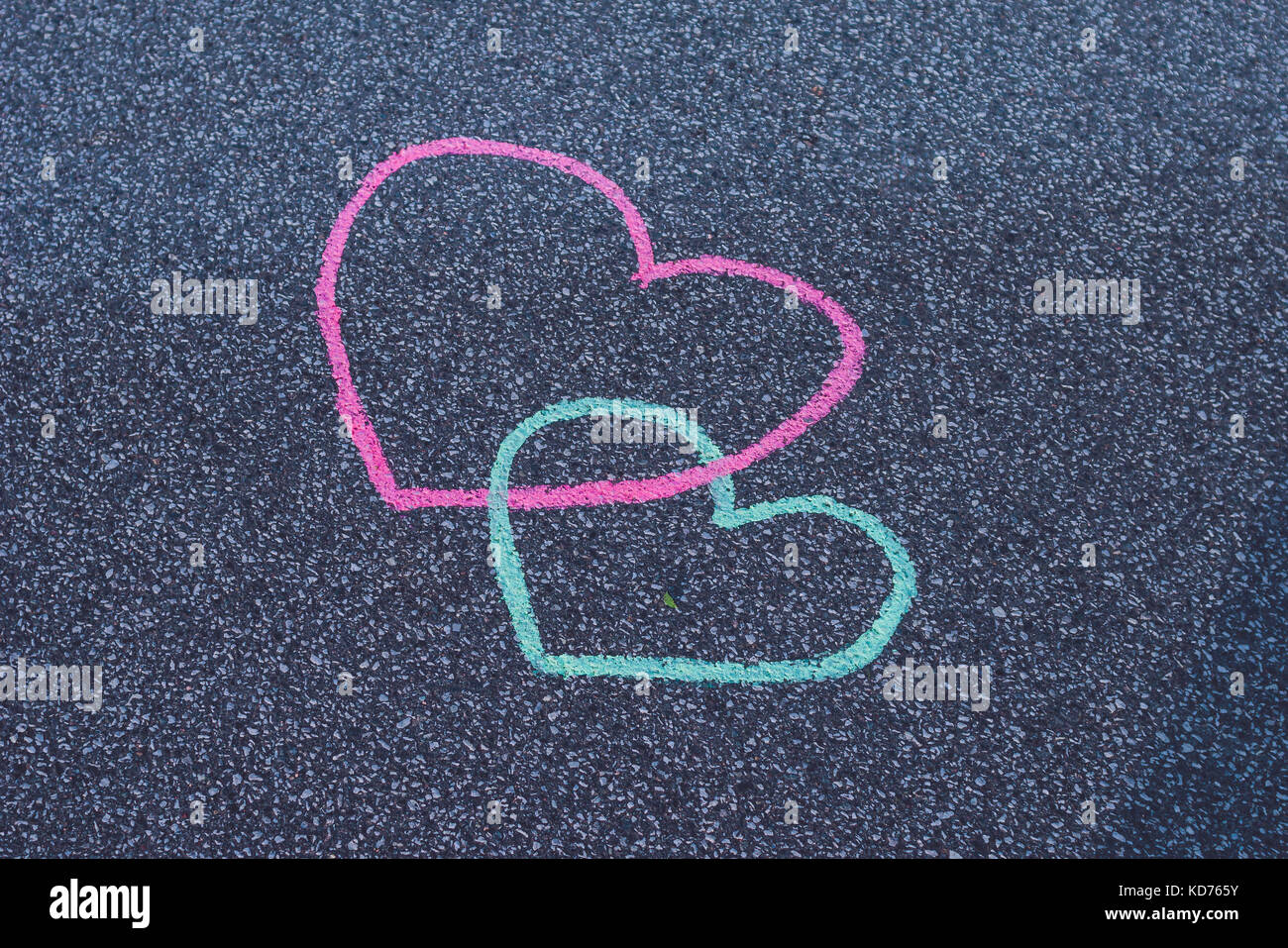 Two hearts drawing chalk on the asphalt - Stock Image