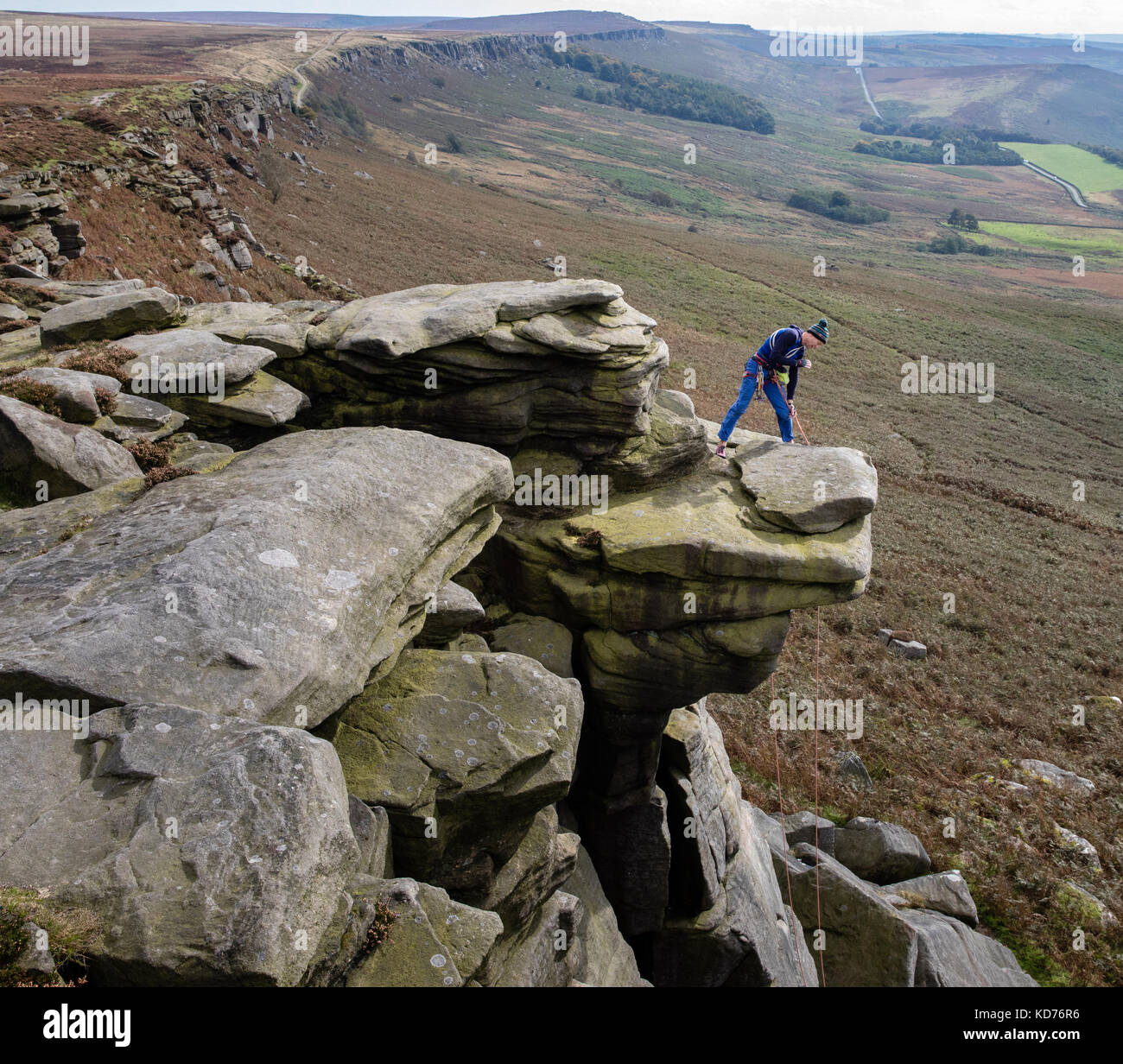 A climber calls down to his climbing buddy from an overhang on Stanage Edge near Hathersage in the Derbyshire Peak - Stock Image