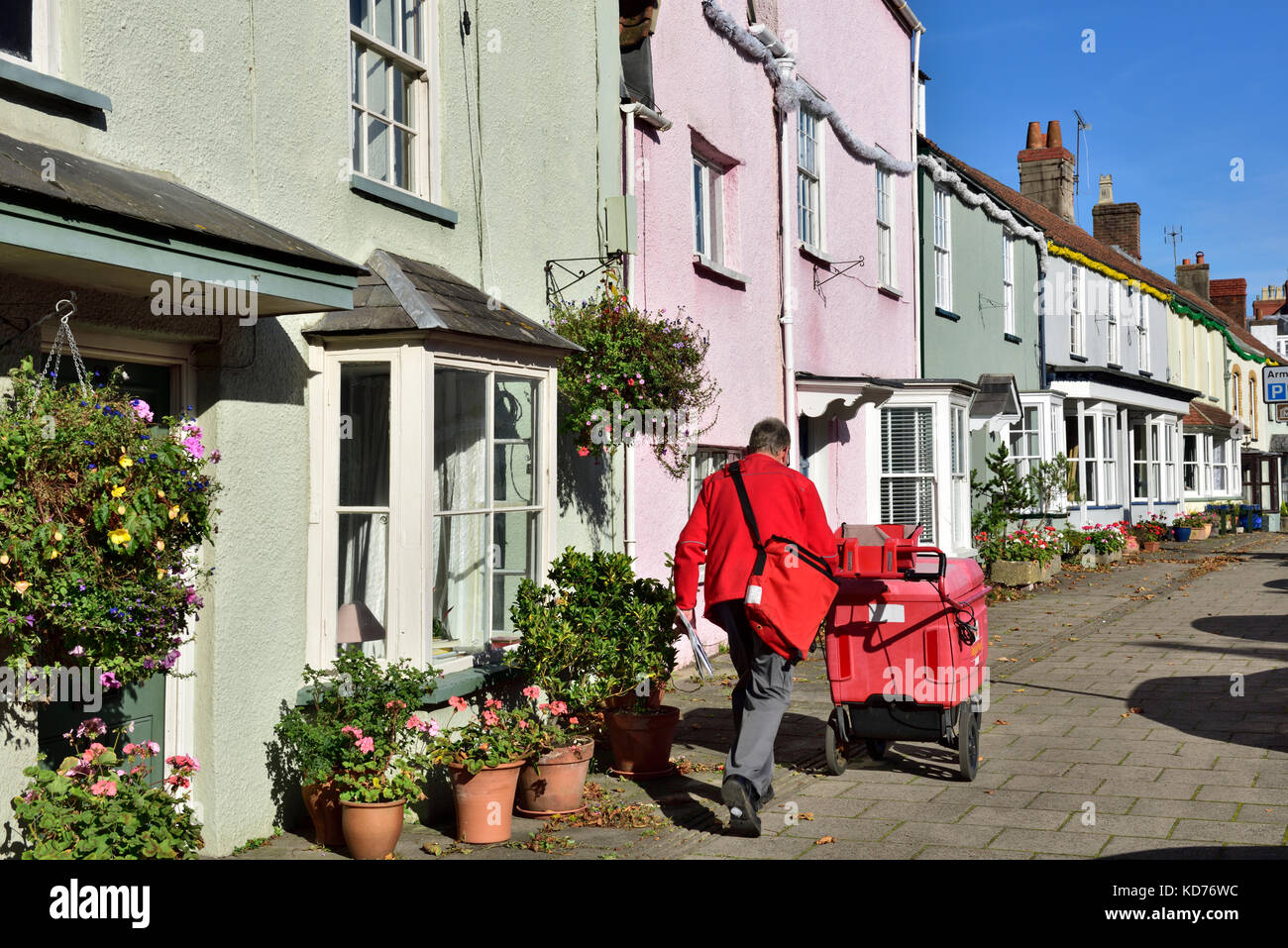 Postman on rounds in row of terrace houses on high street in small English market town of Thornbury, South Gloucestershire Stock Photo