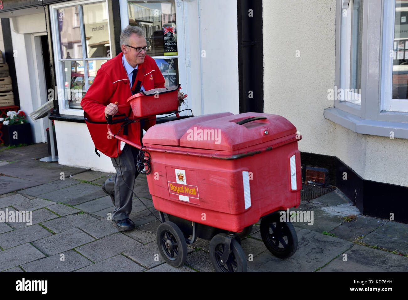 Postman pushing cart making deliveries on rounds in small English market town of Thornbury, South Gloucestershire - Stock Image
