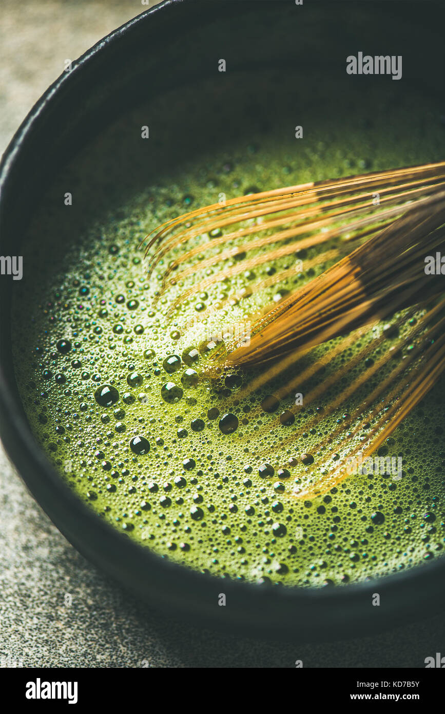 Flat-lay of freshly brewed Japanese matcha green tea, vertical composition - Stock Image