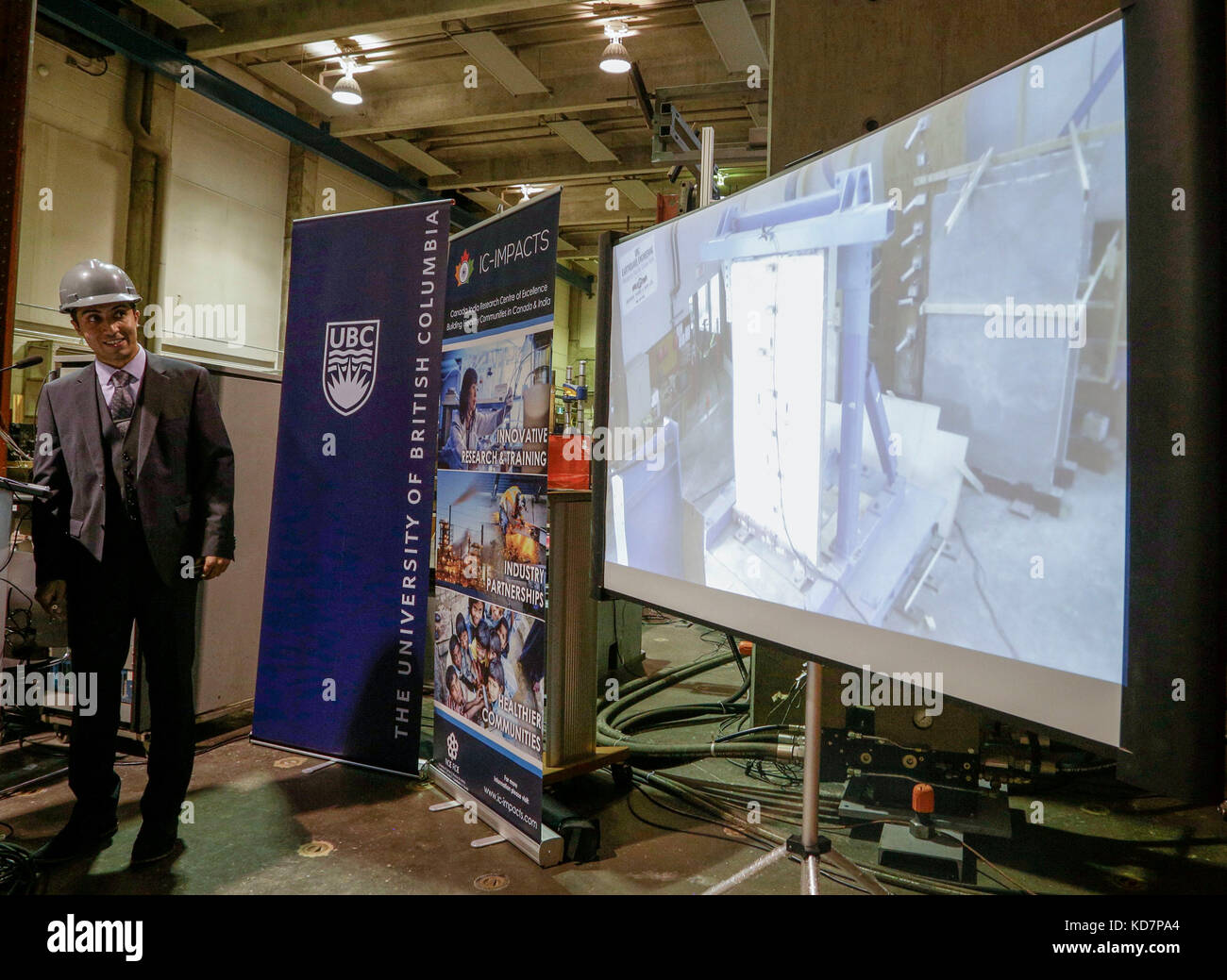 Vancouver. 10th Oct, 2017. A person watches a video showing the concrete wall tested with an earthquake simulator - Stock Image