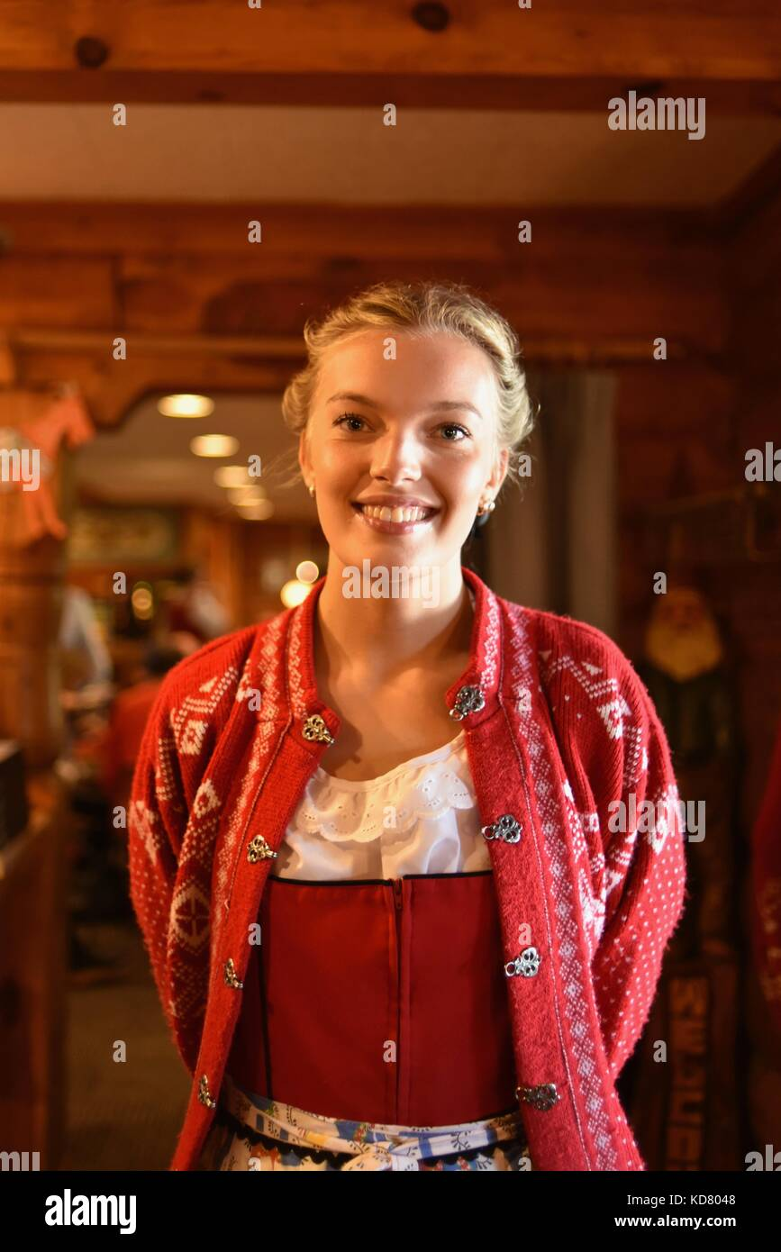 Smiling Swedish waitress greeting restaurant guests at front door of Al Johnson's Swedish Restaurant, Sister - Stock Image