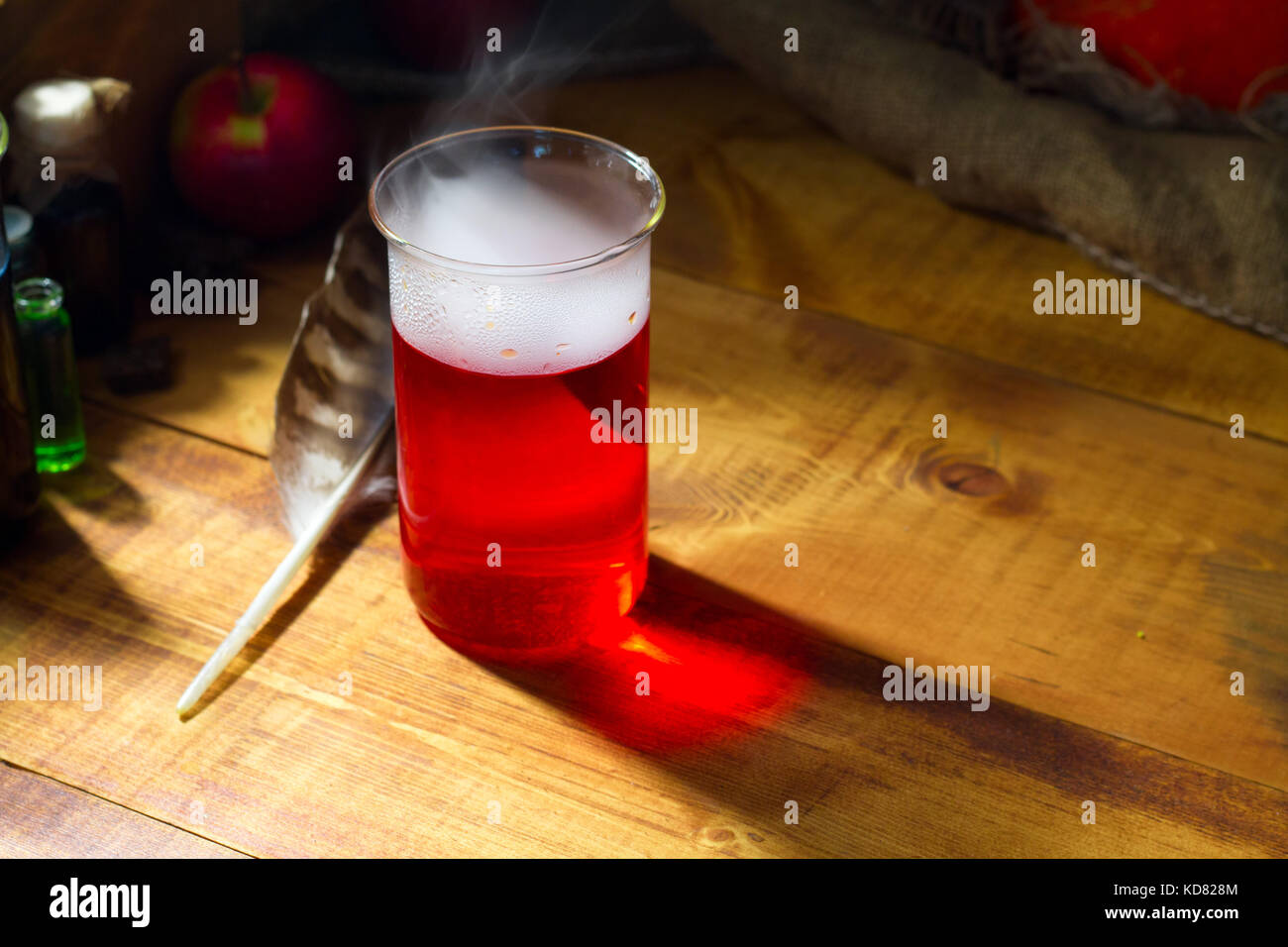 red Potion with smoke or fog on wooden background - Stock Image