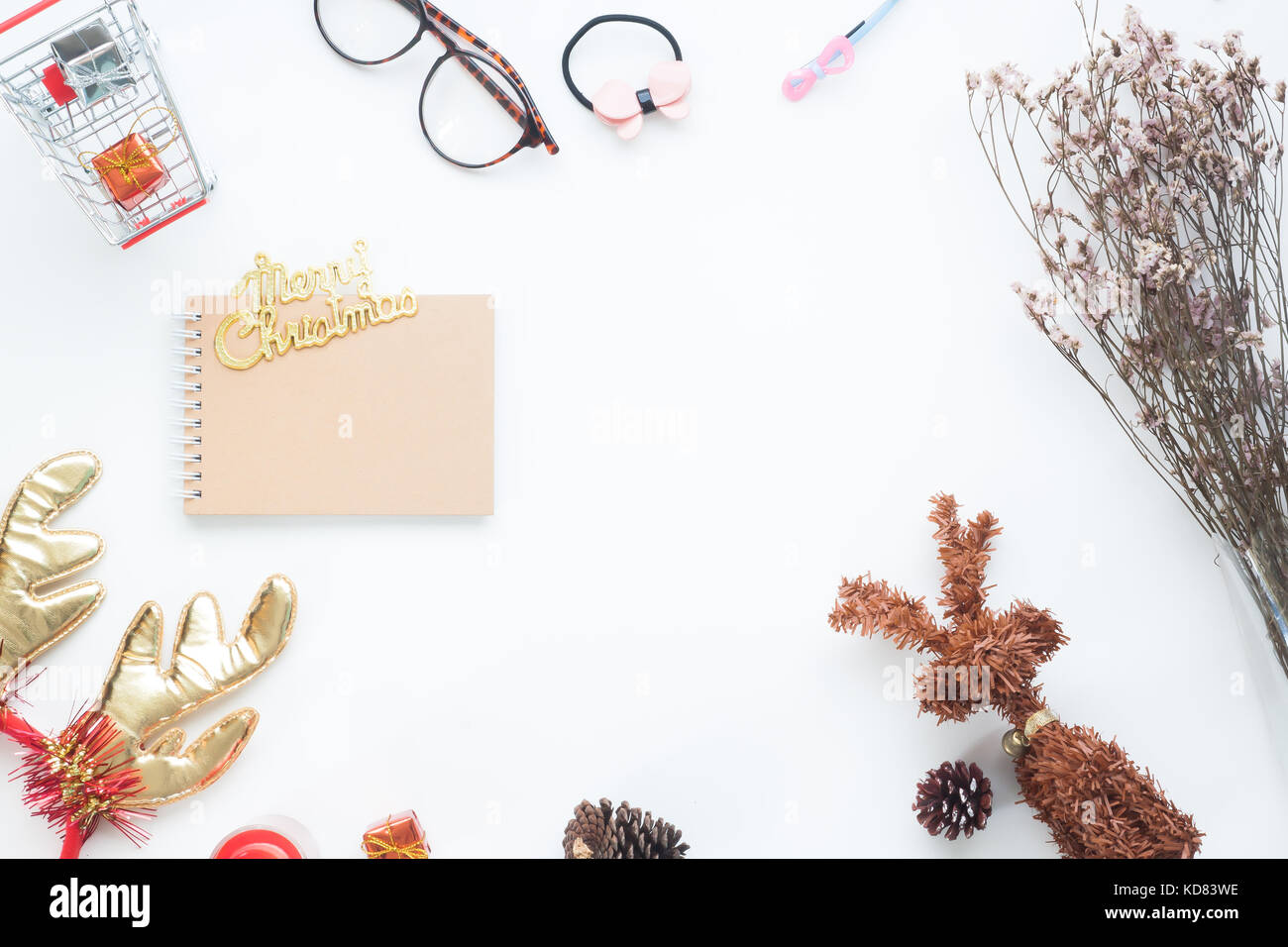 Creative flat lay of Christmas decorations and notebook on white background with copy space - Stock Image