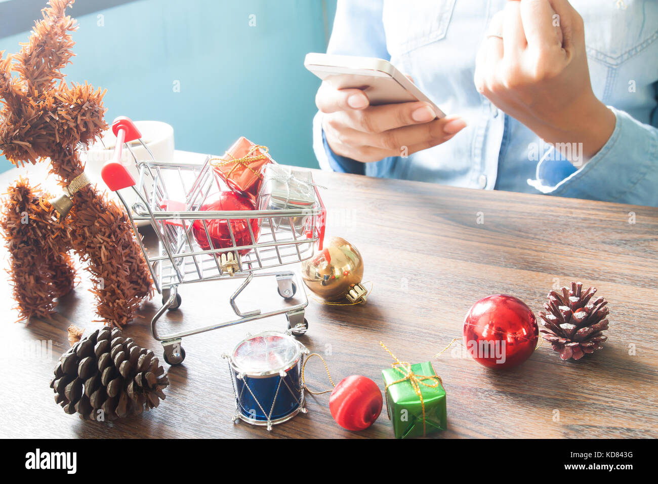 Gift Boxes In Shopping Cart And Christmas Decorations On Table