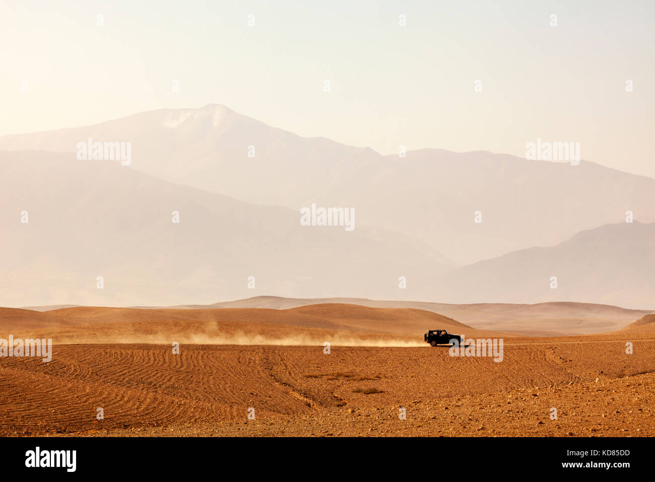 Offroad vehicle driving through Agafay desert, Morocco, Atlas Mountains vanishing in haze - Stock Image