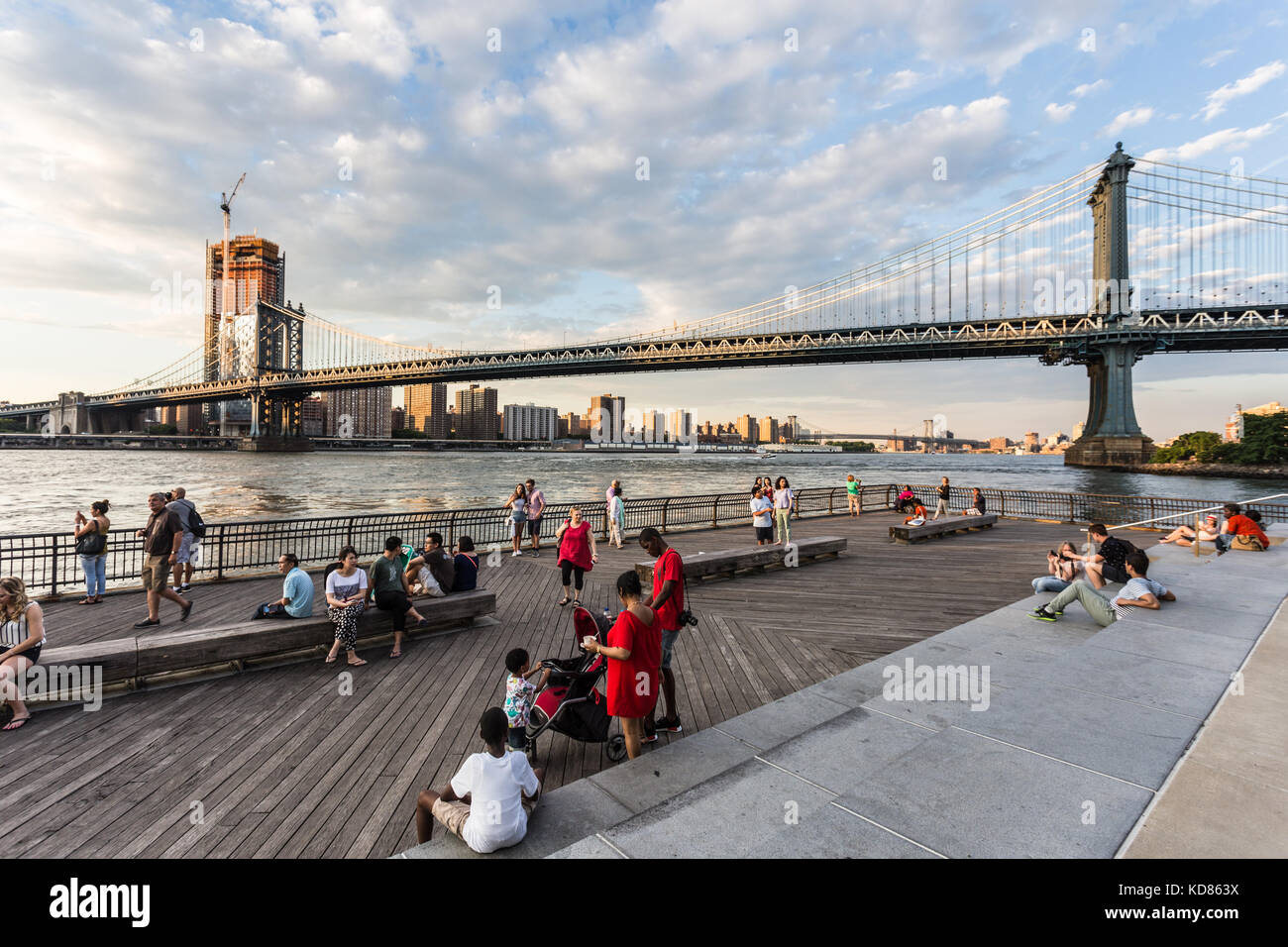 NEW YORK CITY - JULY 3, 2017: People enjoy the sunset over the Manhattan bridge and the East river from the Brooklyn - Stock Image