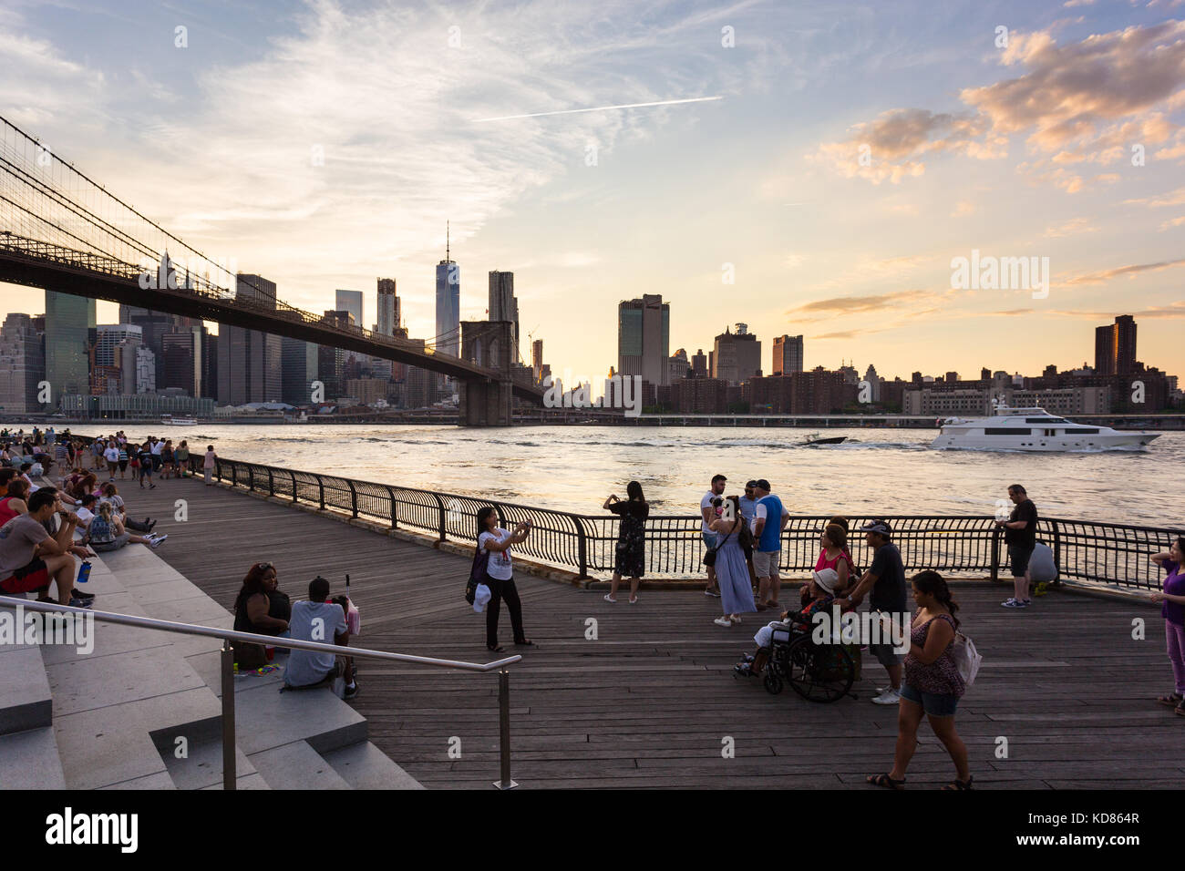 NEW YORK CITY - JULY 3, 2017: People enjoy the sunset over the Manhattan financial district and the East river from - Stock Image