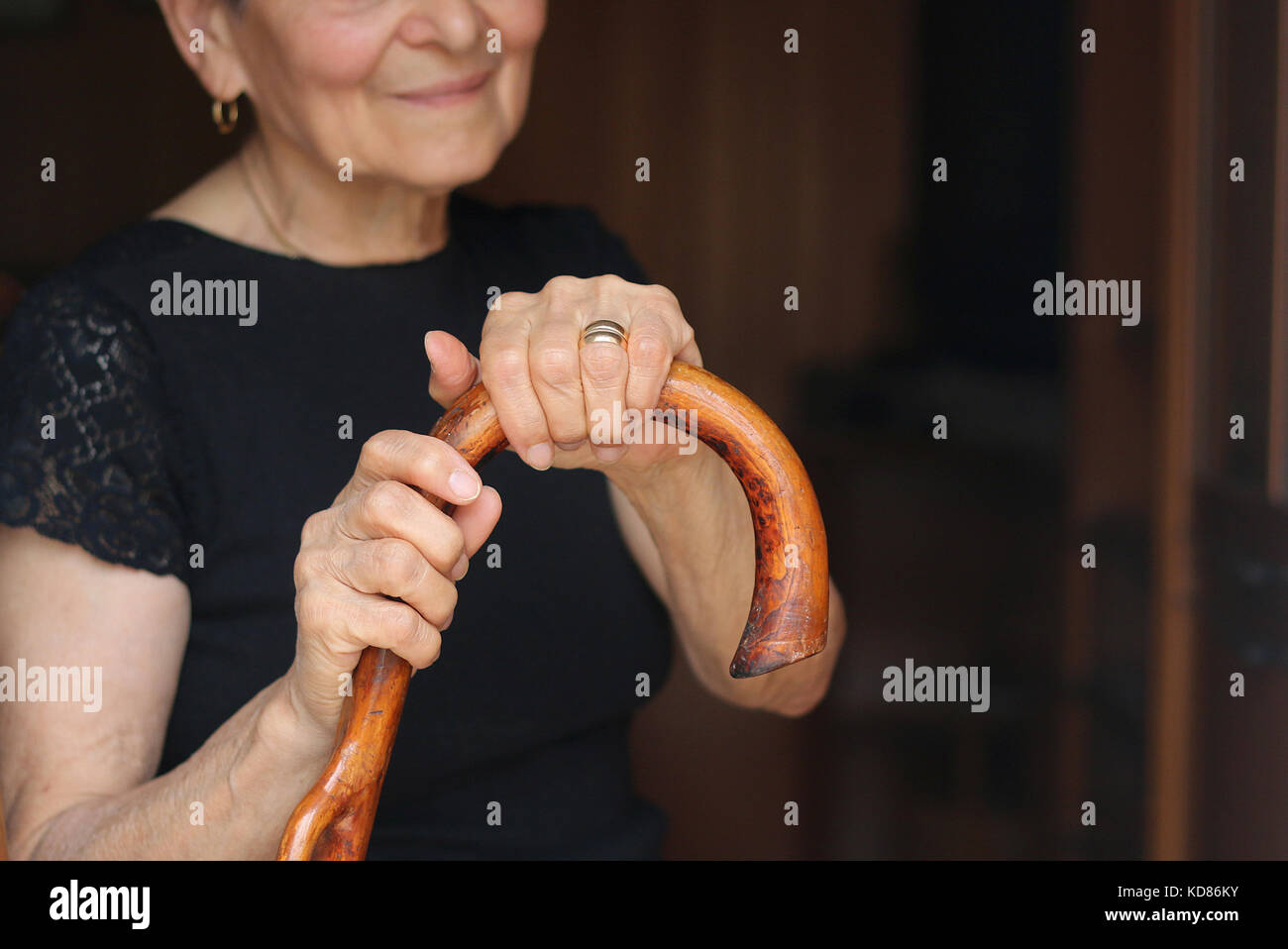 Senior woman holding a walking stick - Stock Image