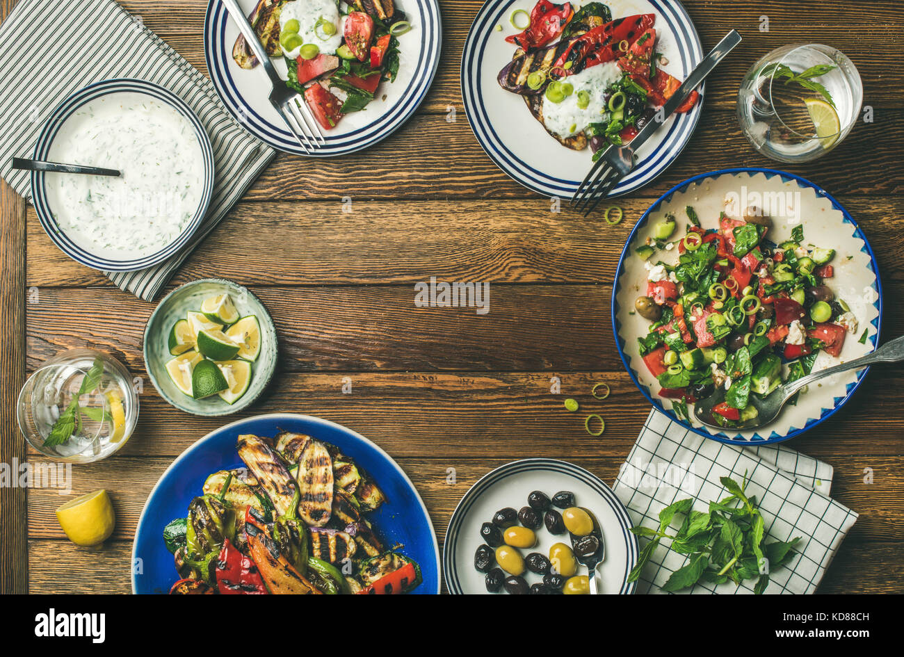 Flat-lay of healthy dinner table setting. Fresh salad, grilled vegetables with yogurt sauce, pickled olives over - Stock Image