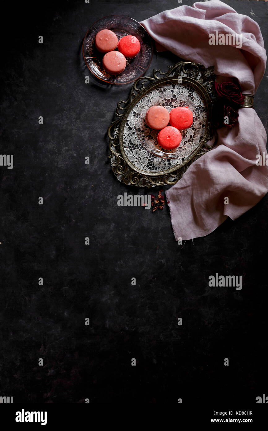 Macarons on a silver platter against a dark bckground Stock Photo