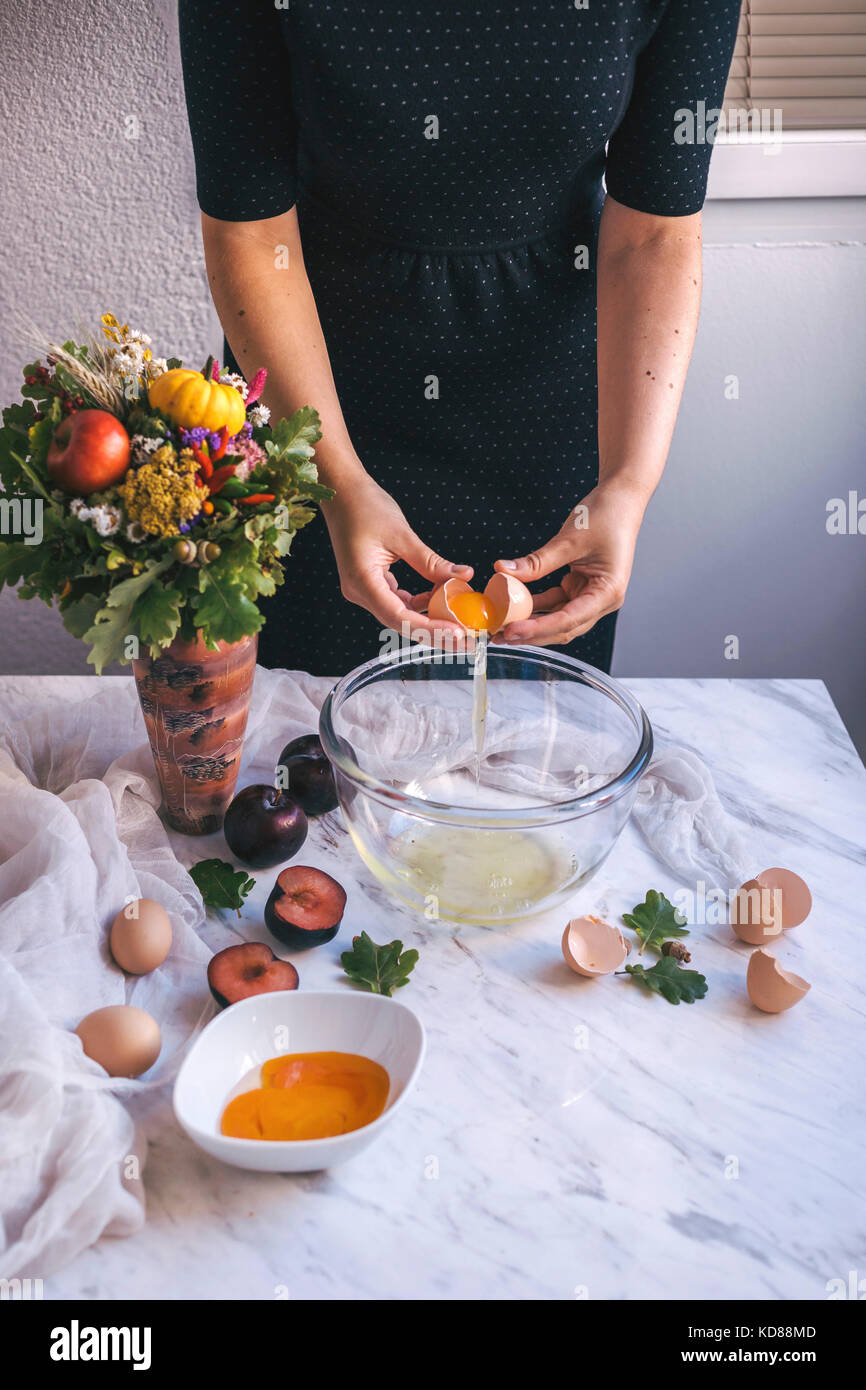 Woman separating eggs whites and yolks in a bowl while baking a cake - Stock Image