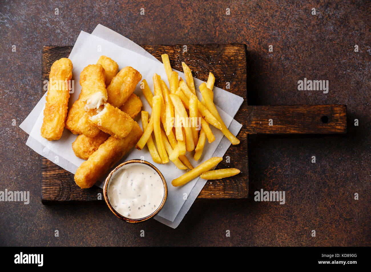Fish fingers and Chips british fast food with tartar sauce on dark background Stock Photo