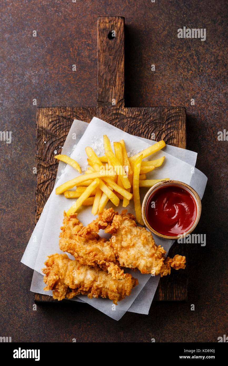 Fish and Chips british fast food with ketchup sauce on dark background - Stock Image