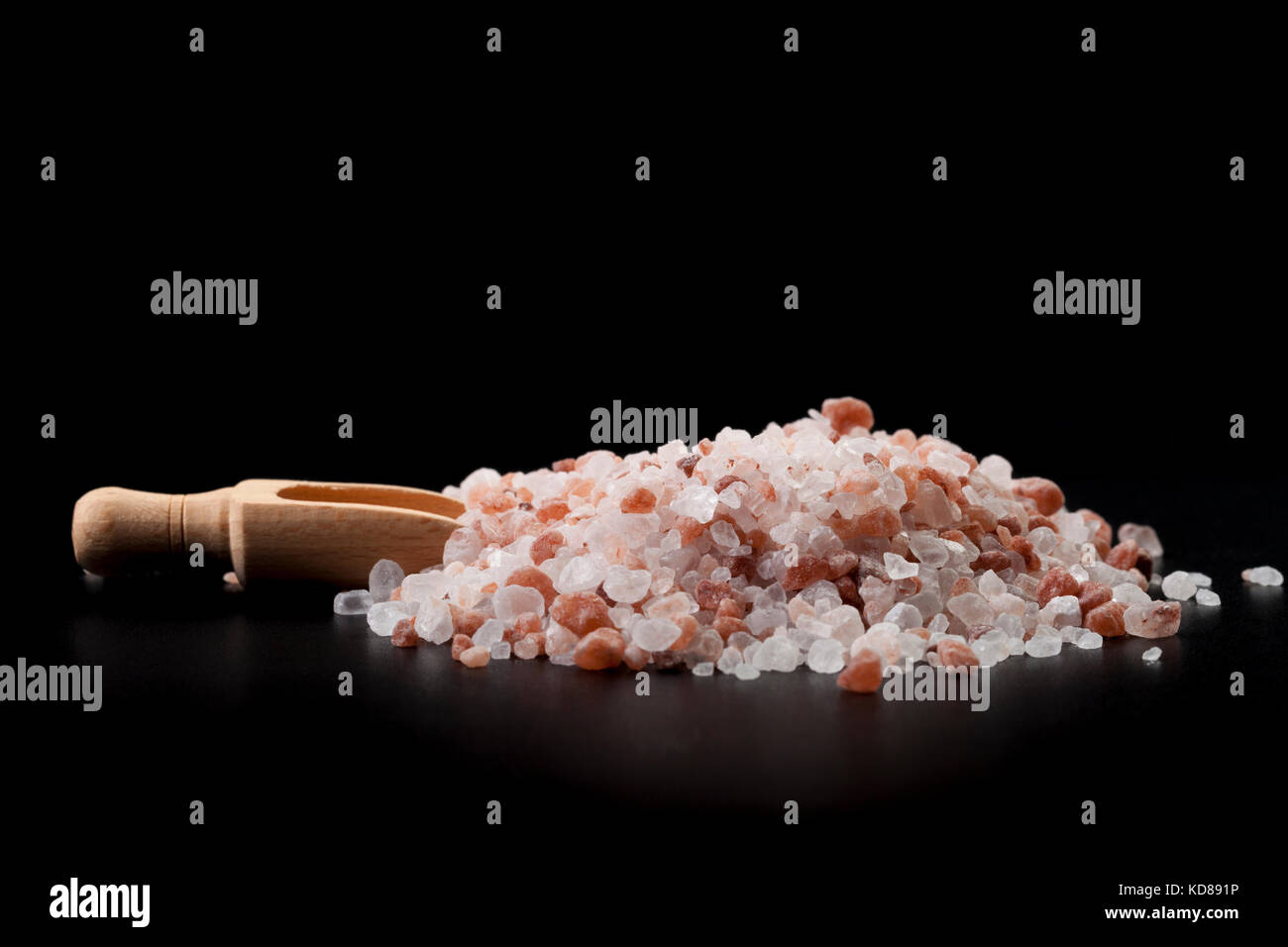 Brown Wood Spice Spoon With Hymalaian Salt Crystals on Black Background - Stock Image