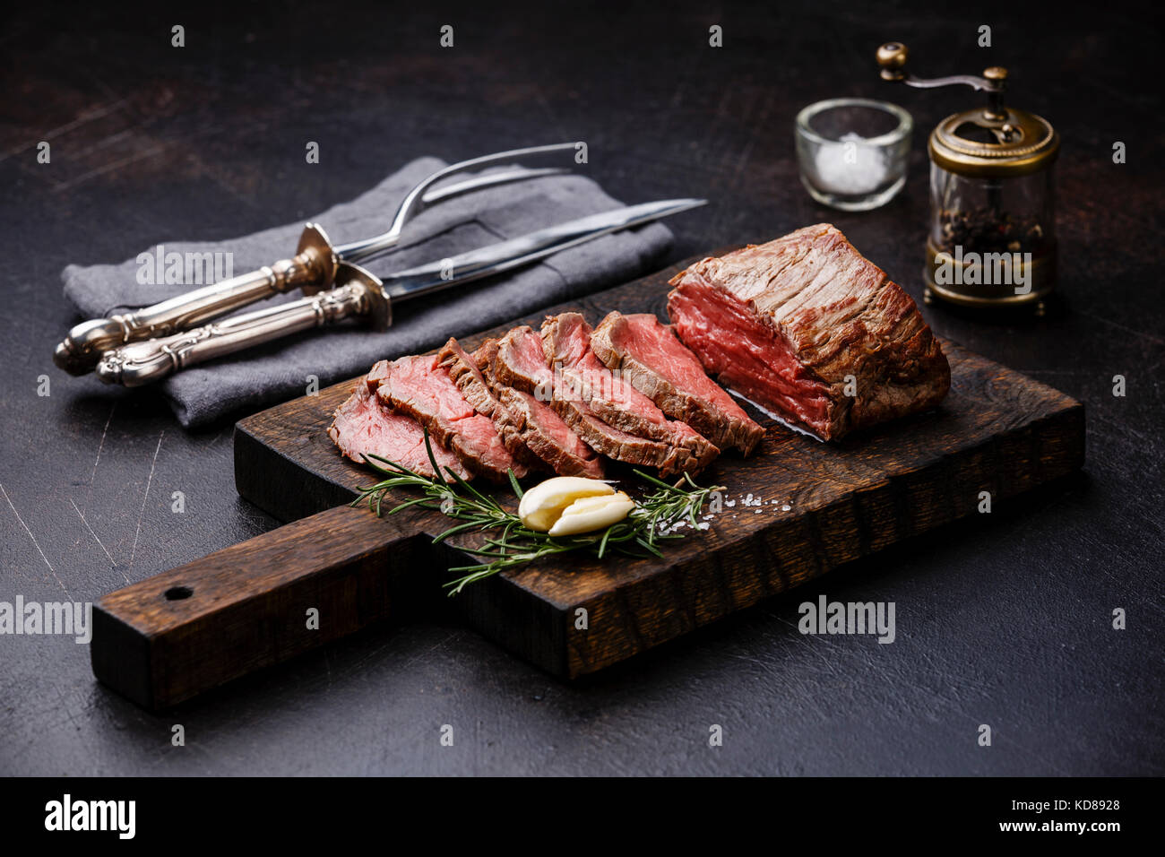 Sliced Tenderloin meat Roast beef on cutting board with knife and fork carving set, saltcellar and pepper mill - Stock Image