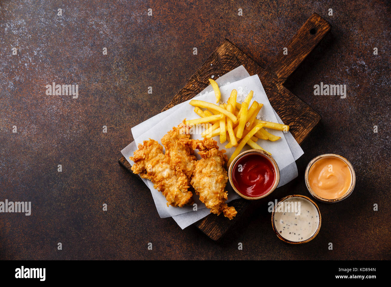 Fish and Chips british fast food with three popular sauce for choice on brown background copy space - Stock Image
