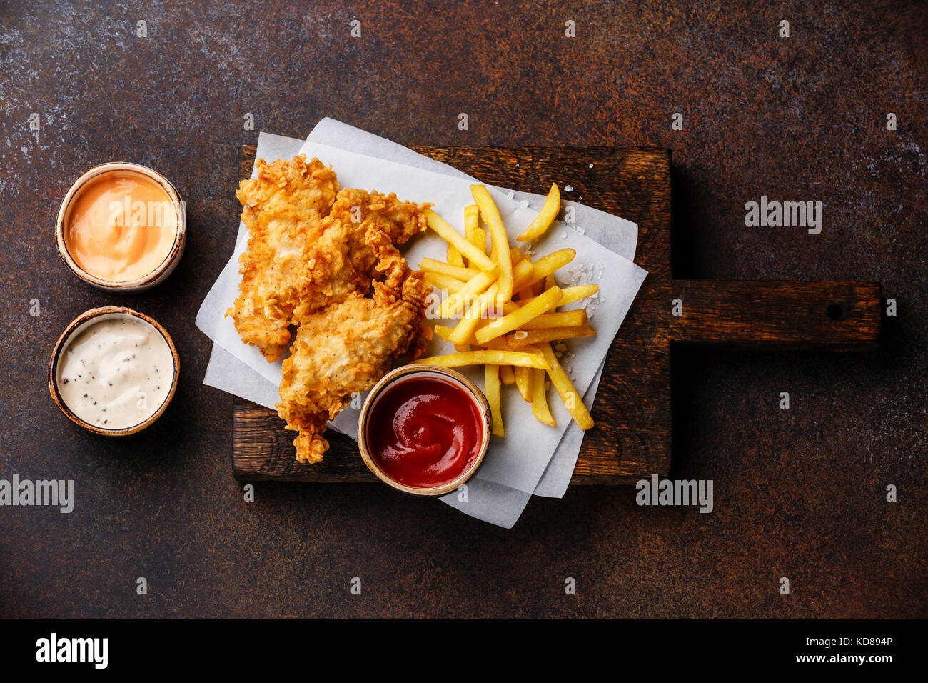 Fish and Chips british fast food with three popular sauce for choice on brown background - Stock Image