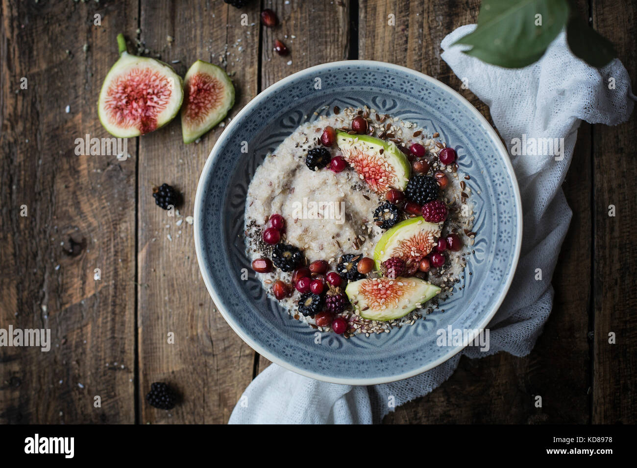 Breakfast: oatmeal pudding with fresh fruit on wooden table - Stock Image