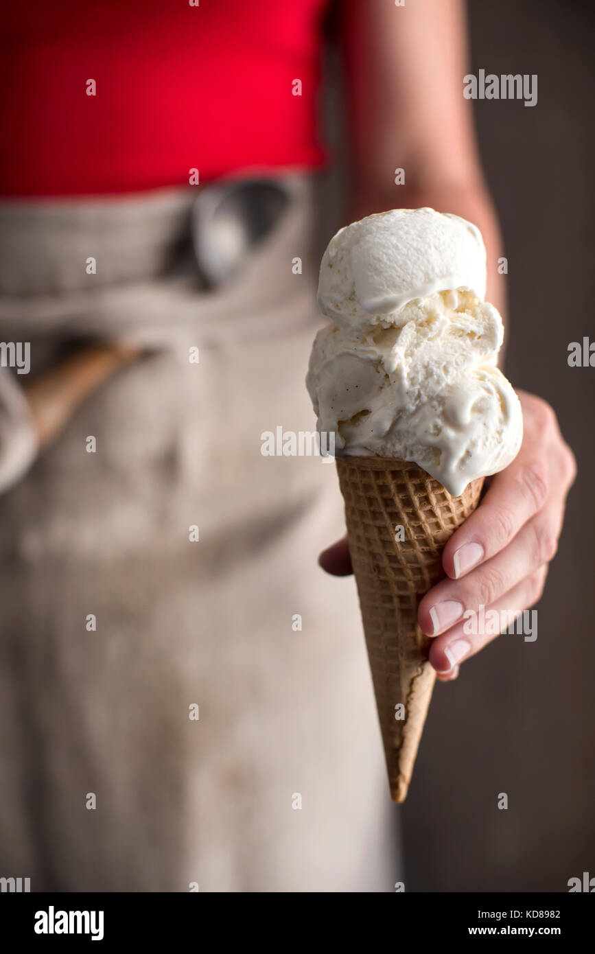 Woman wearing a red shirt and linen apron holding out a freshly scooped vanilla ice cream cone. - Stock Image