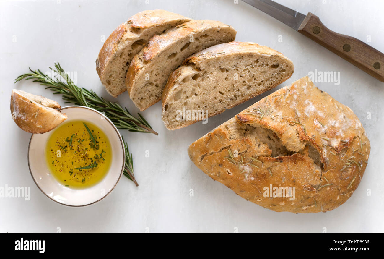 Rustic loaf of artisinal, rosemary bread sliced on marble surface with bowl of oil and fresh herbs. - Stock Image
