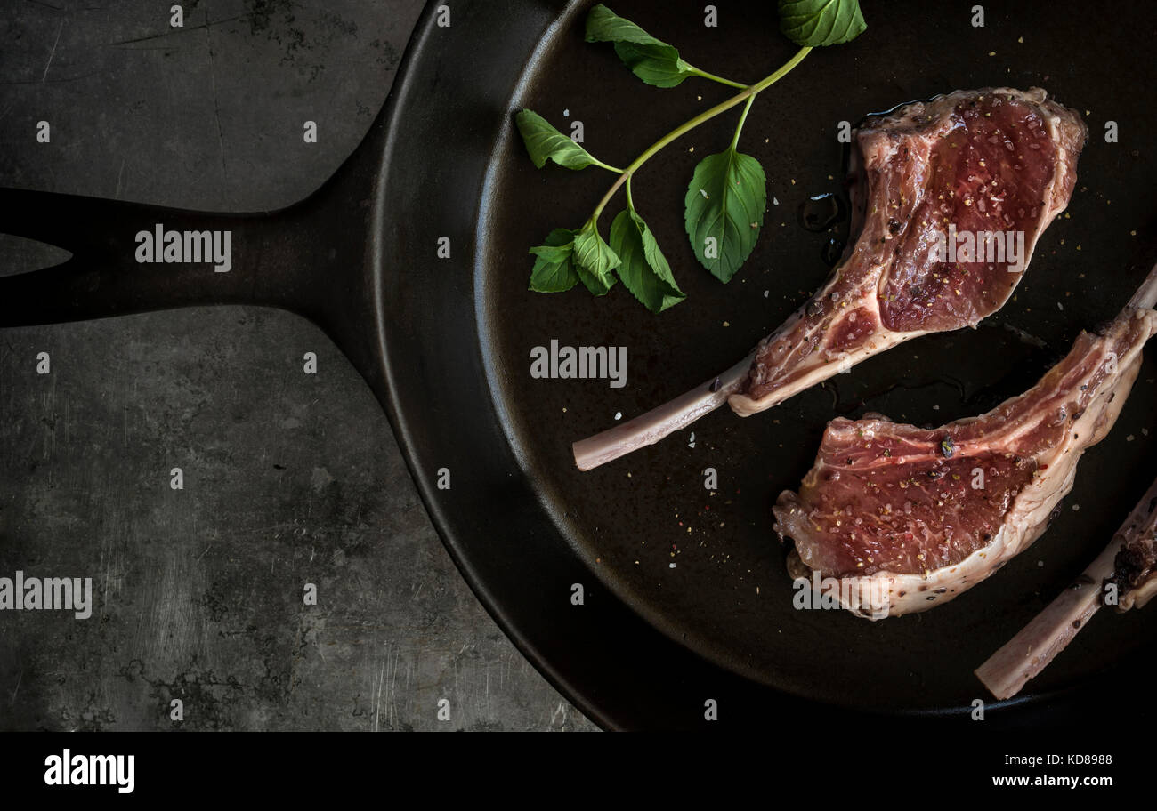 Raw lollipop lamb chops in cast iron skillet with seasonints and fresh basil. - Stock Image