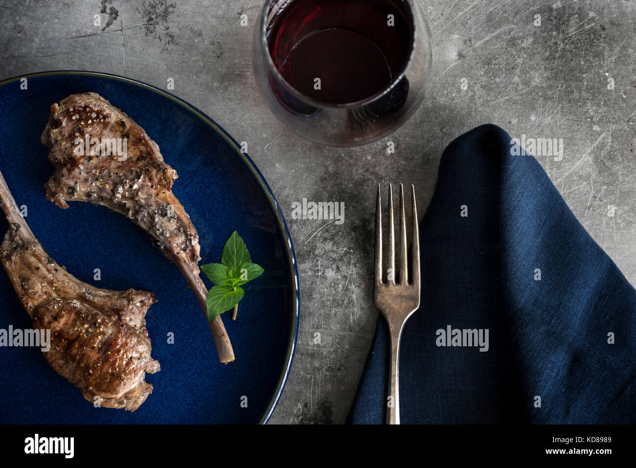 Roasted lollipop lamb chops on blue plate. Table setting with navy linen, red wine and rustic metal surface. - Stock Image
