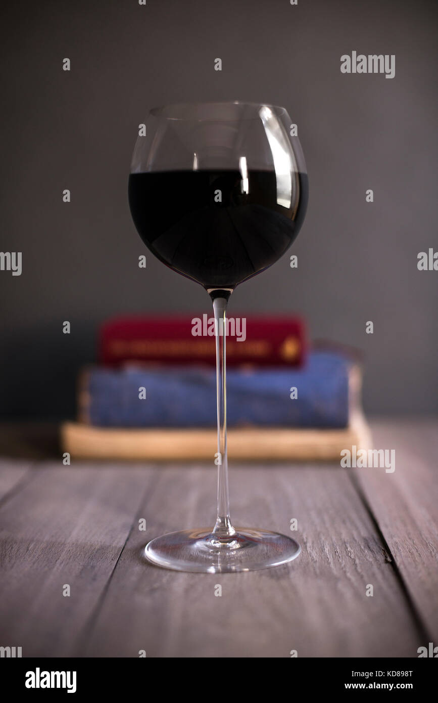 A delicate stemmed glass of red wine in front of a stack of vintage books on a rustic wood surface. - Stock Image