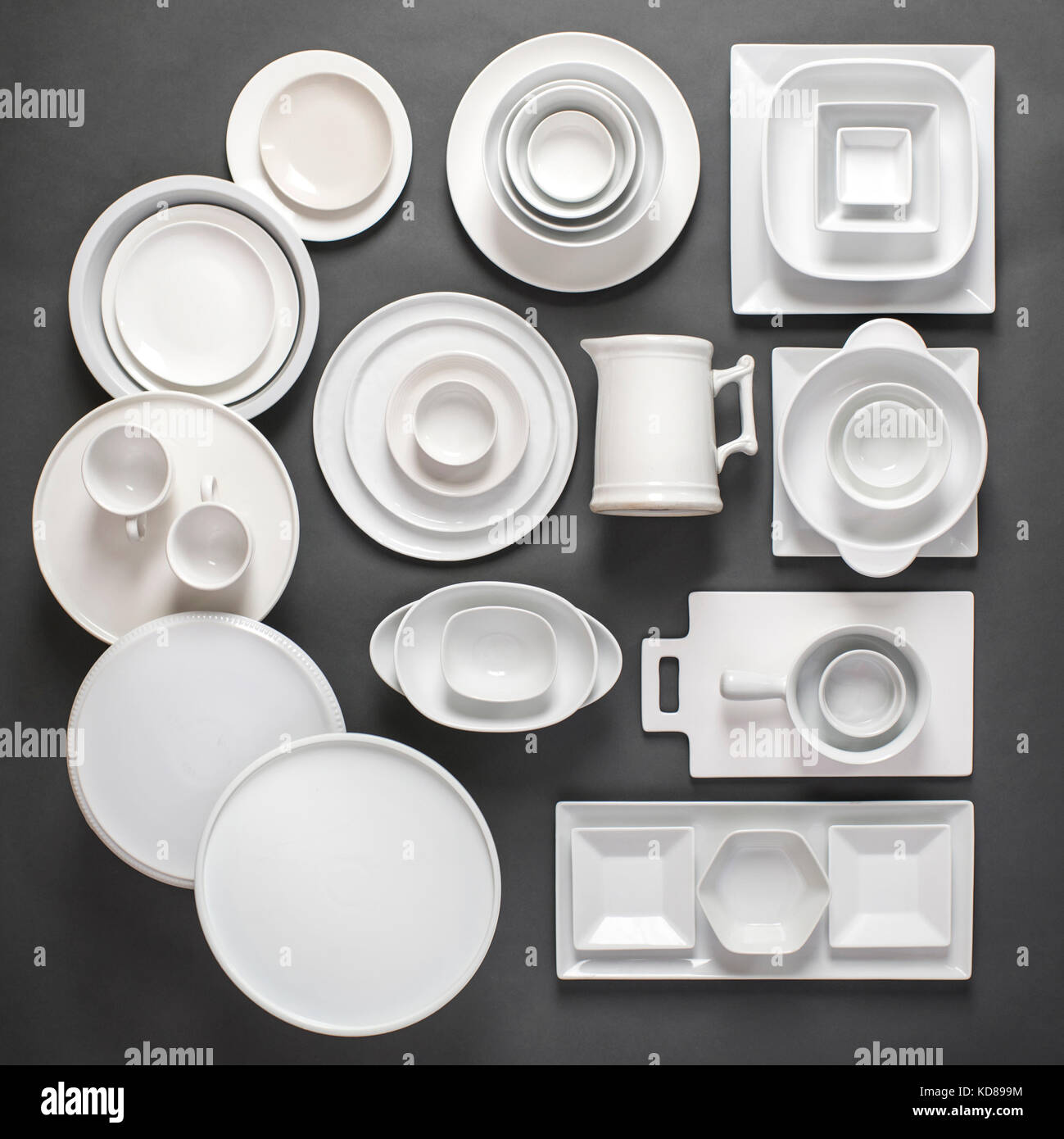 Assorted variety of white porcelain dinnerware laid out in a grpahic, organized way on a gray background. - Stock Image