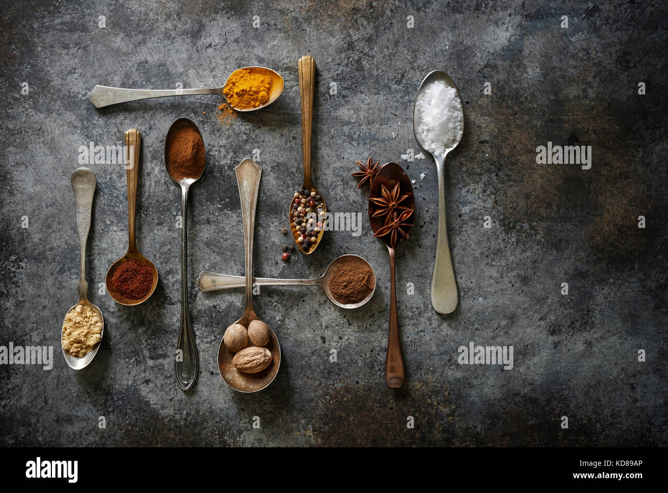 An array of beautifully laid out baking and cooking spices in vintage spoons on a rustic dark surface. - Stock Image