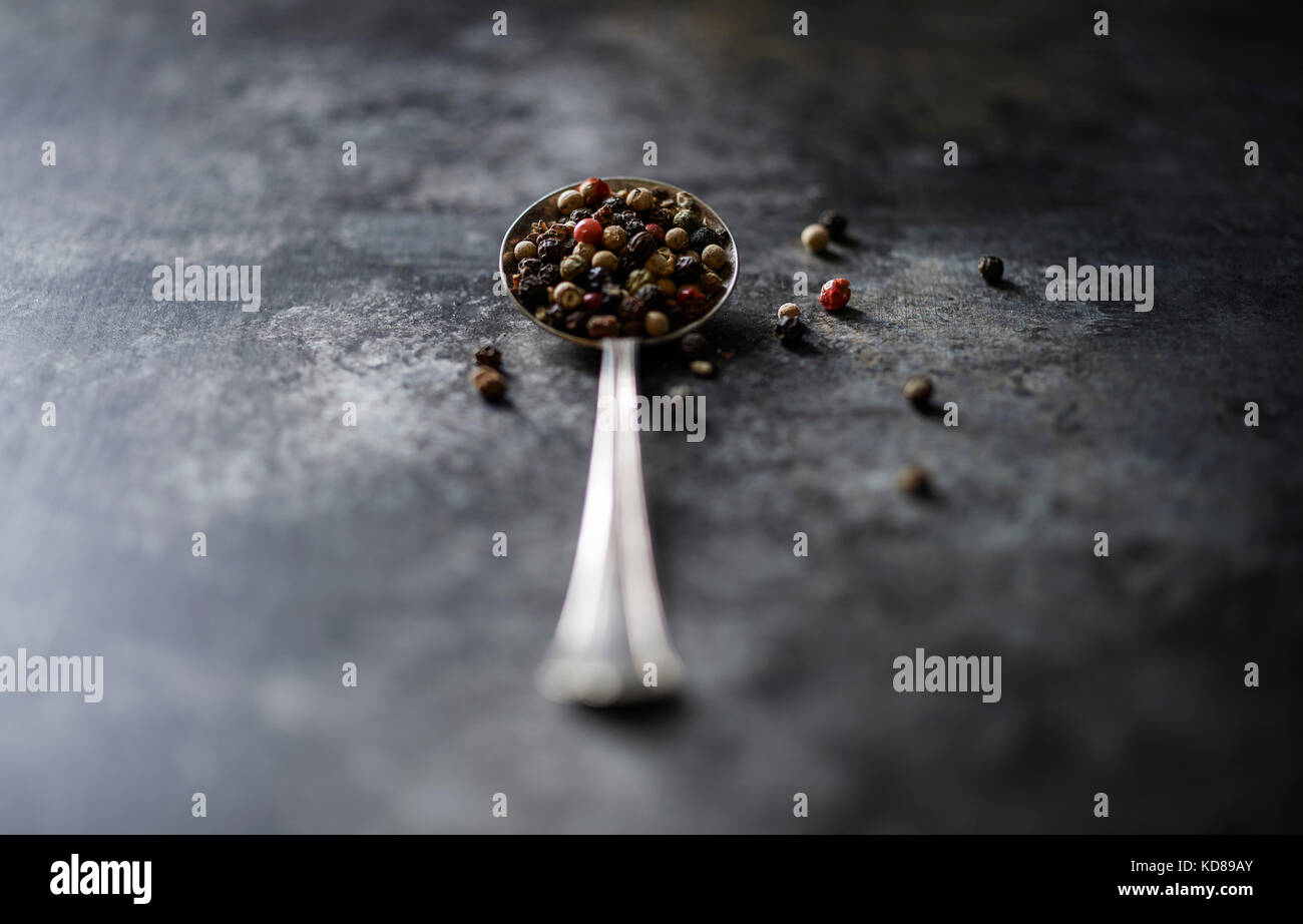 A vintage spoon filled with beautiful tri-color peppercorn on a dark rustic surface. - Stock Image