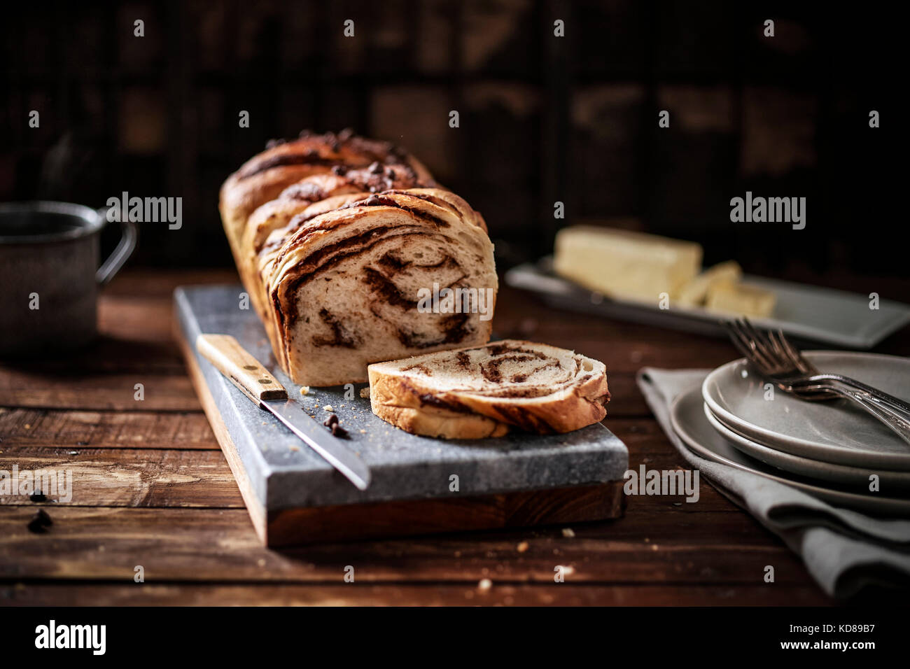 Warm loaf of chocolate braided bread on a marble board in a rustic wood setting. - Stock Image