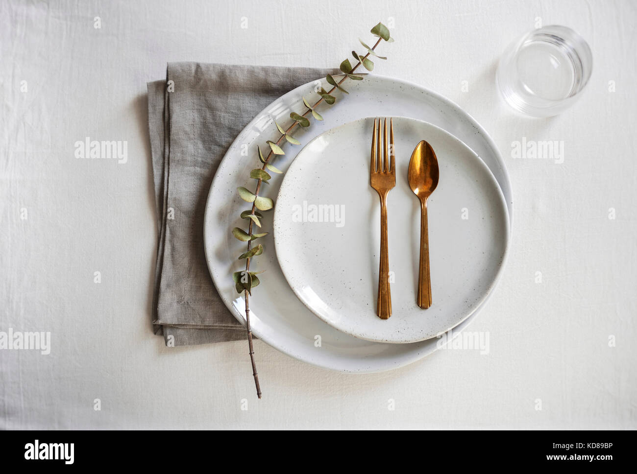 A beautiful, minimal table setting with organic, handmade gray plates, gold flatware and a natural linen. - Stock Image