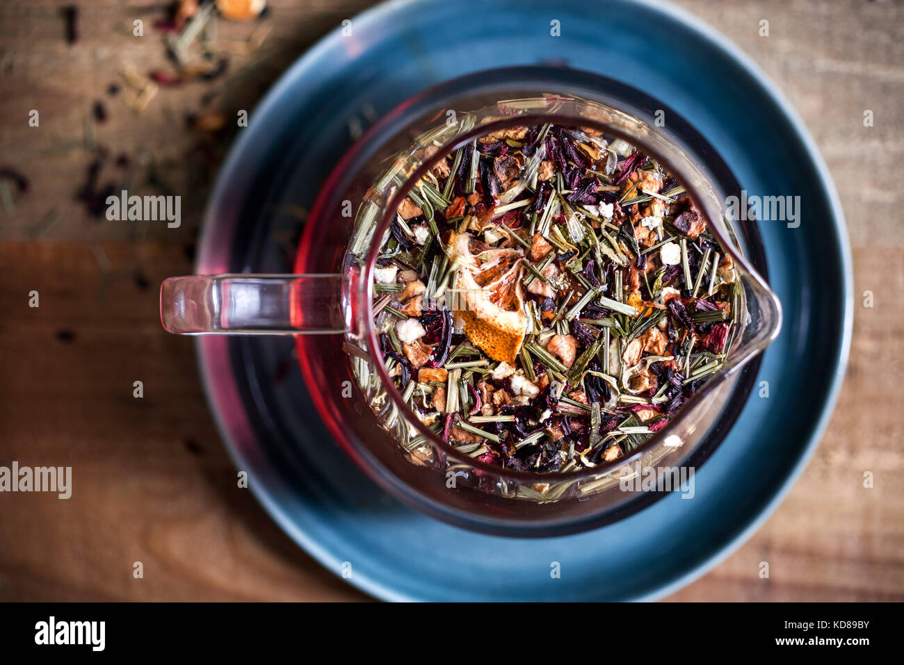 Detail shot of textured loose leaf tea floating in a glass teapot on a warm wood surface. - Stock Image
