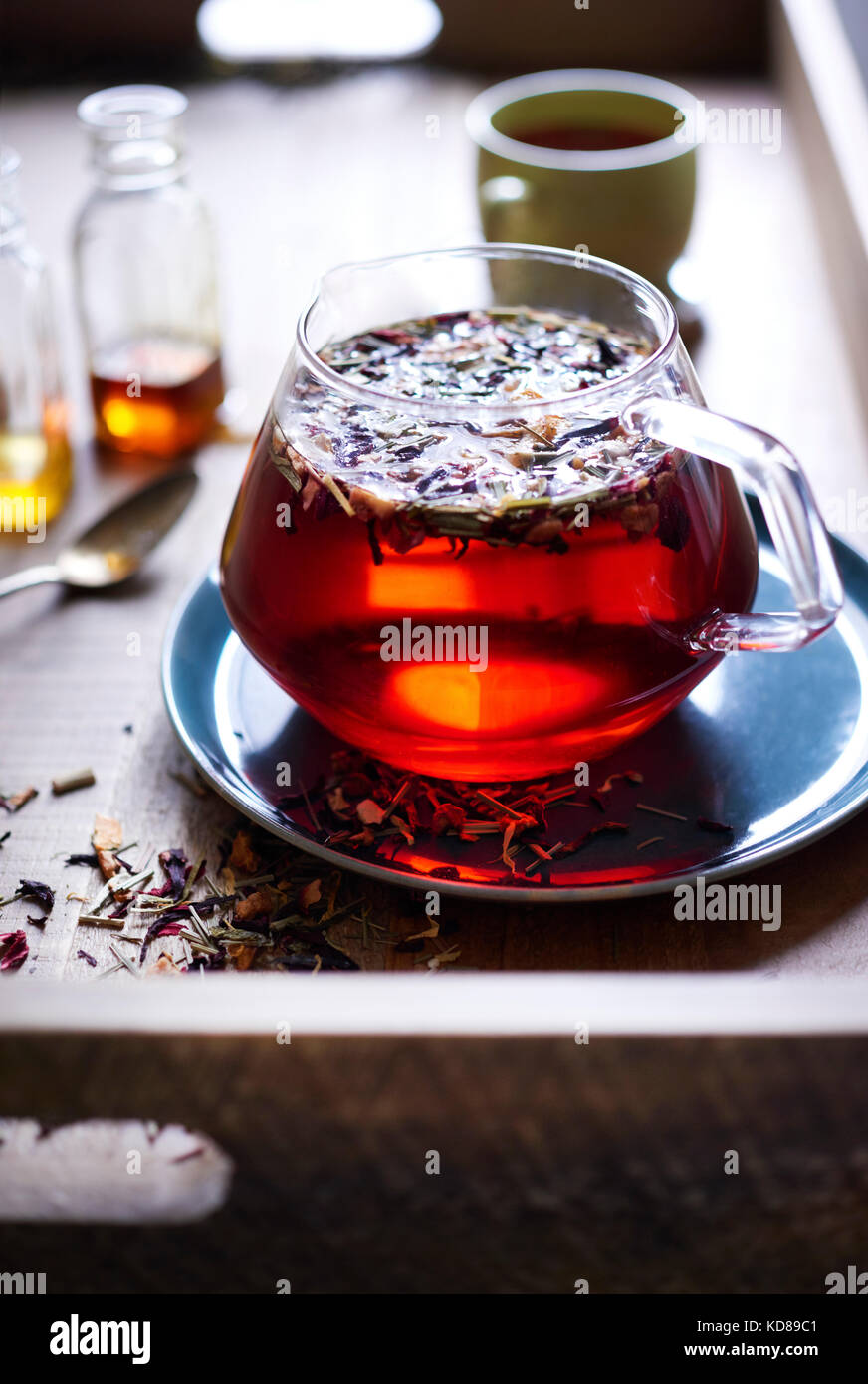 A bright airy scene of a warm wood tea tray with loose leaf tea floating in red tea in a glass teapot with honey - Stock Image