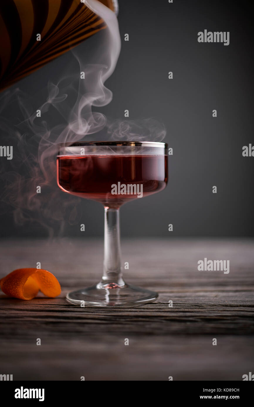 Red cocktail in vintage coupe glass with smoke pouring in on a rustic, gray wood surface. - Stock Image