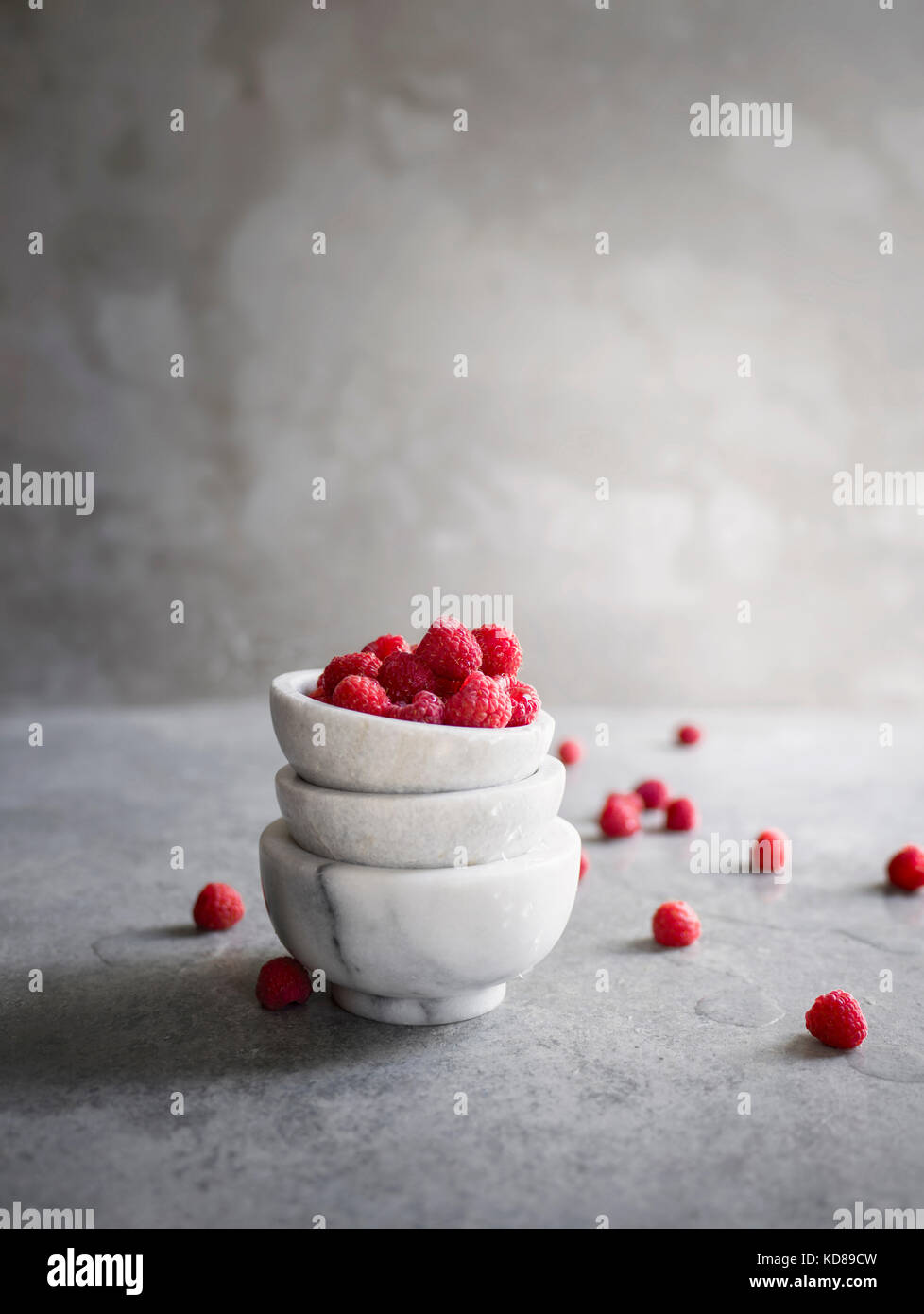 Fresh raspberries in stacked marble bowls on textured metal surface. Light and airy. - Stock Image