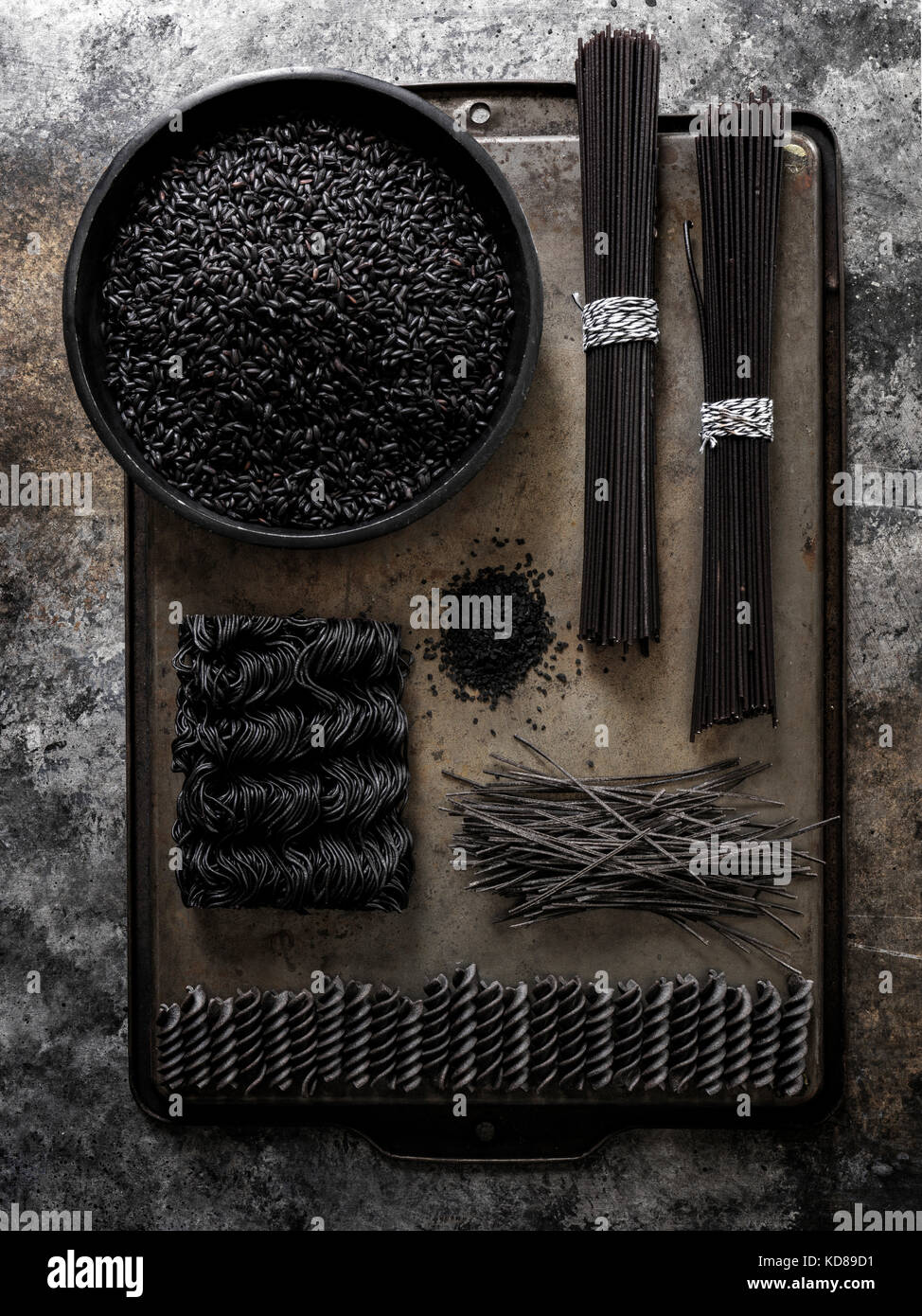 A geometric layout of black pastas (rice, spaghetti, ramen, etc…) on a dark metal surface with a lot of texture - Stock Image