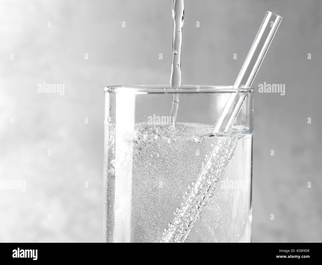 Detail of sparkling water being poured into a clear glass with a clear straw on a gray metal background. - Stock Image