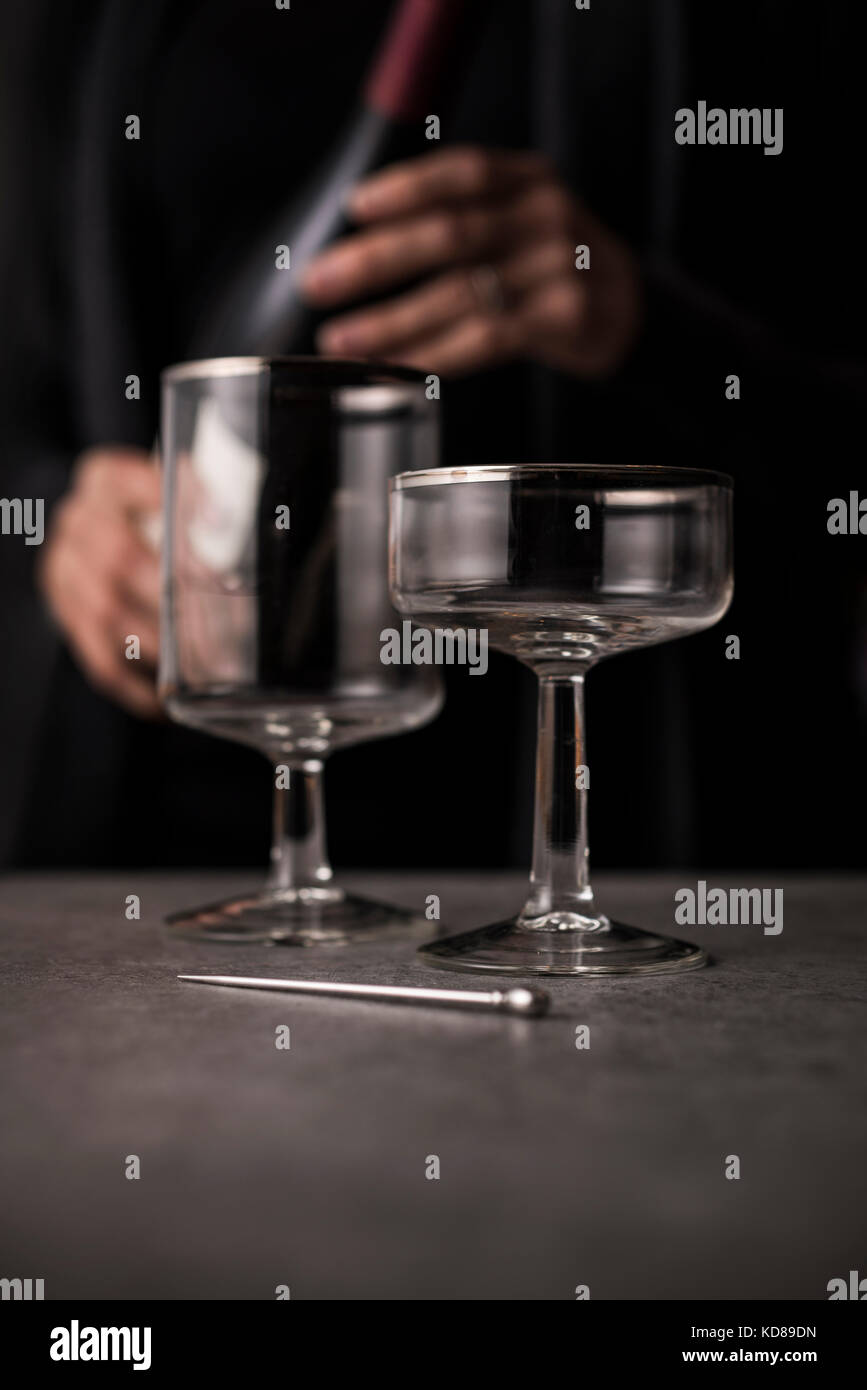 Antique, high end wine glasses with sommelier in background with bottle of red wine. - Stock Image