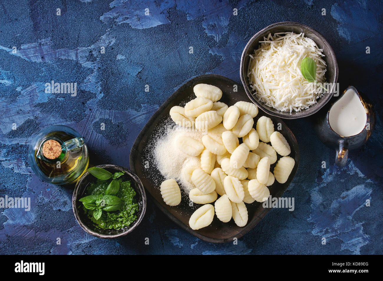 Raw uncooked potato gnocchi in black wooden plates with ingredients. Flour, grated parmesan cheese, pesto sauce, - Stock Image
