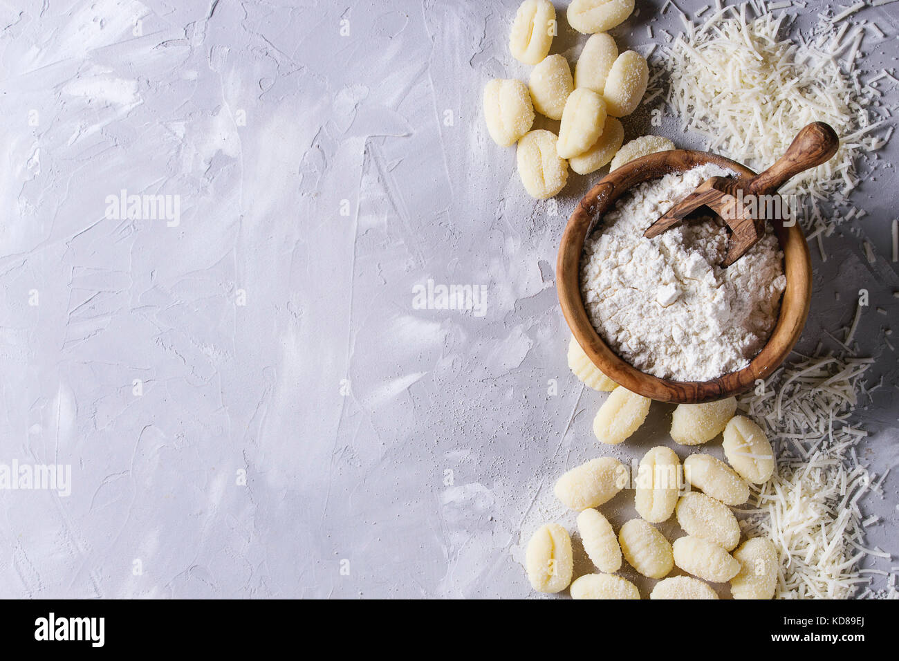 Raw uncooked potato gnocchi with olive wood bowl of flour, grated parmesan cheese over gray concrete background. - Stock Image