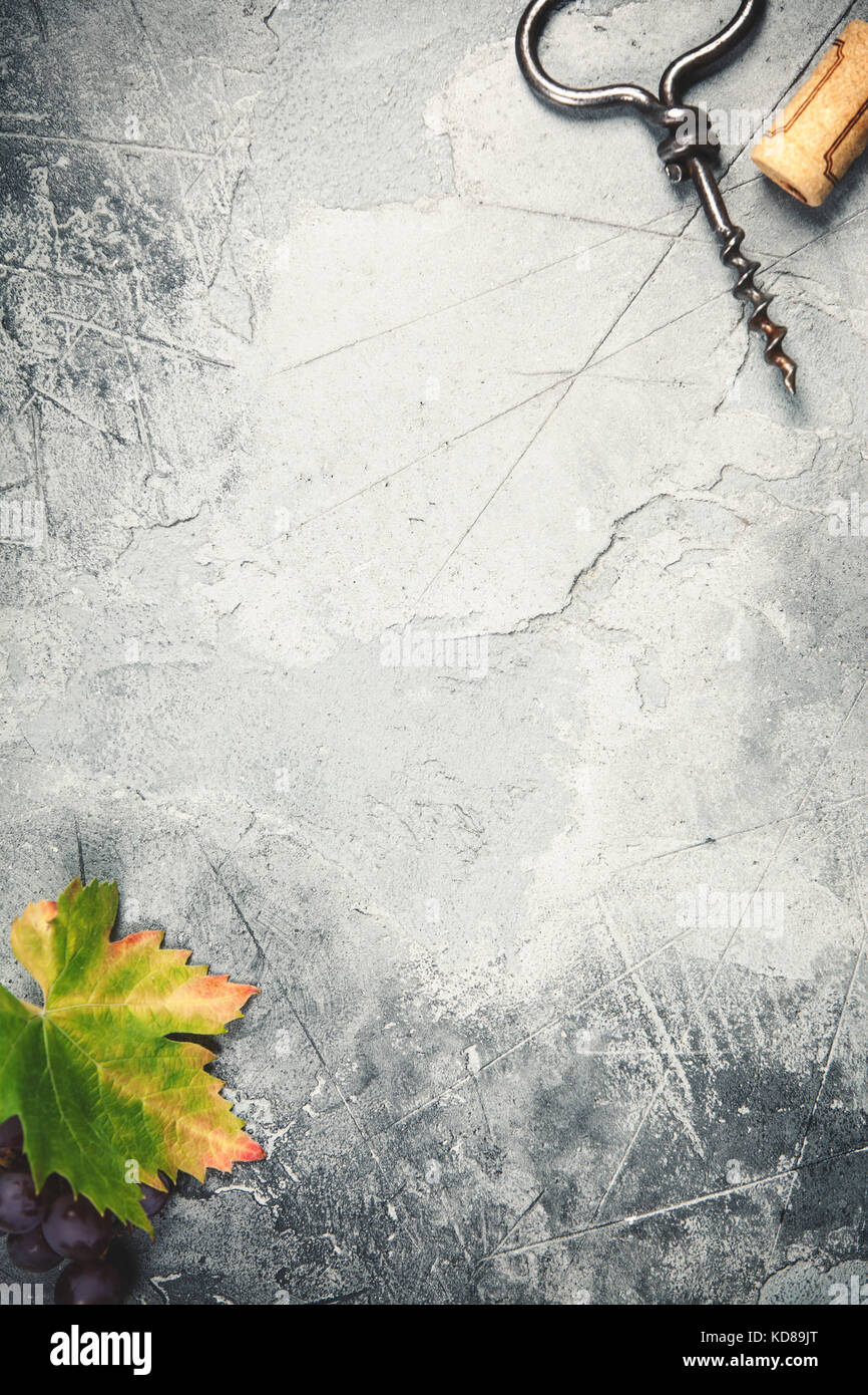 Top view of an old cork screw and grape leaf on gray concrete background with space for text.  A vertical design - Stock Image