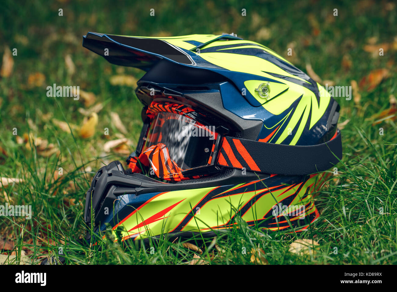 motorcycle helmet with glasses for protection dry fallen leaves over greem grass. Automne Stock Photo
