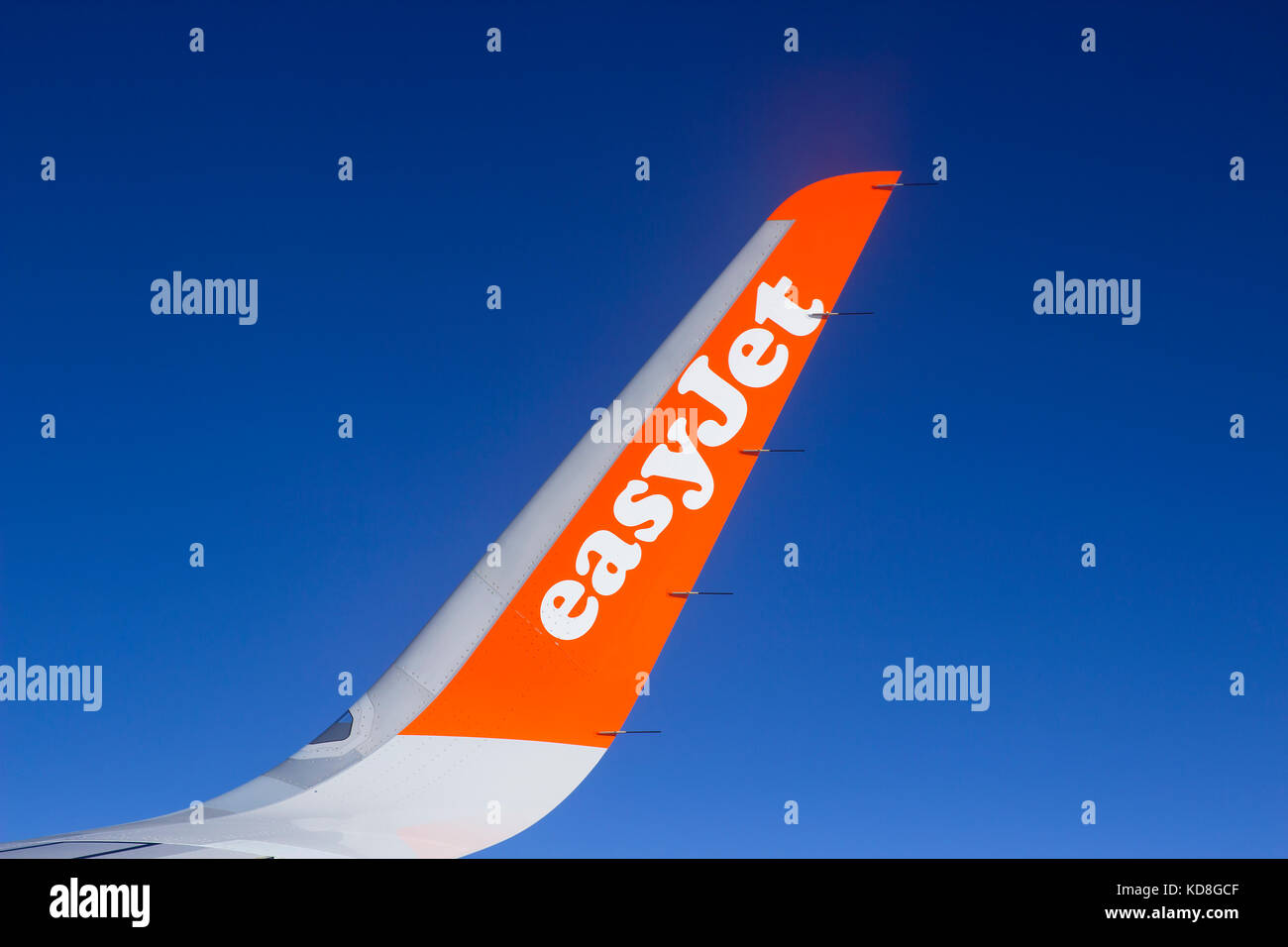 The wing and winglets of an Airbus A320 commercial airliner with a company logo while in flight - Stock Image